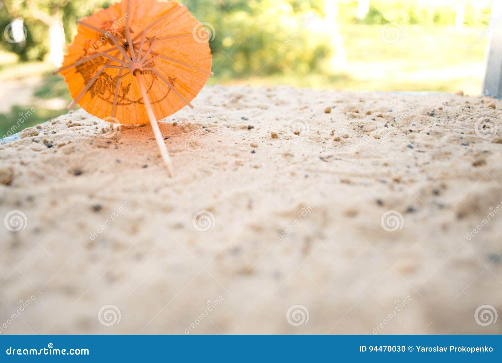 鸡尾酒的伞在含沙夏天背景