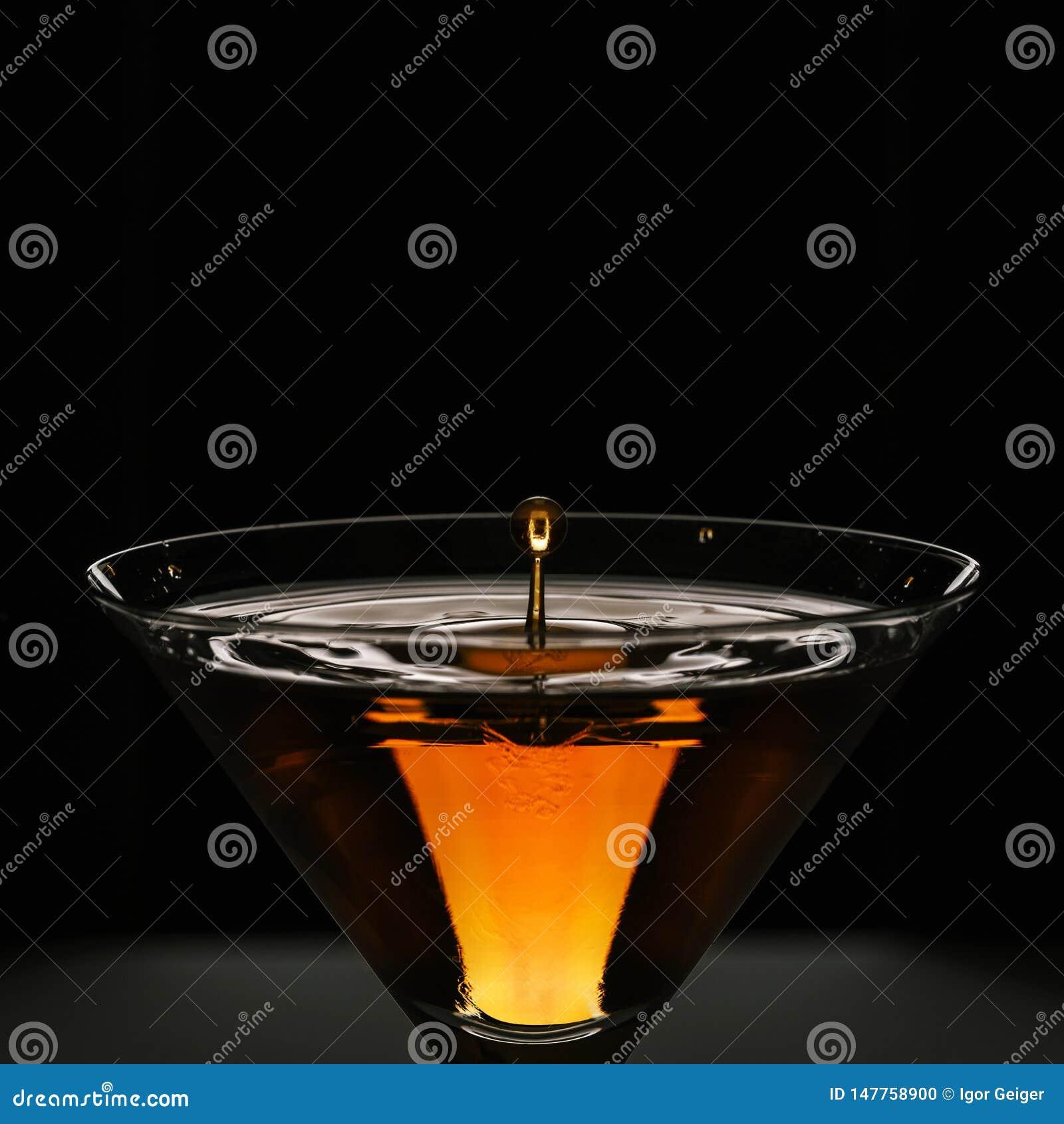 鸡尾酒黄色红色在马蒂尼鸡尾酒的贝加尔湖与小滴特写镜头美丽的飞溅