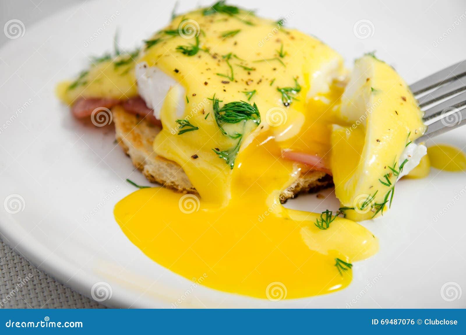鸡蛋本尼迪克特在一块白色板材的早餐,液体卵黄质