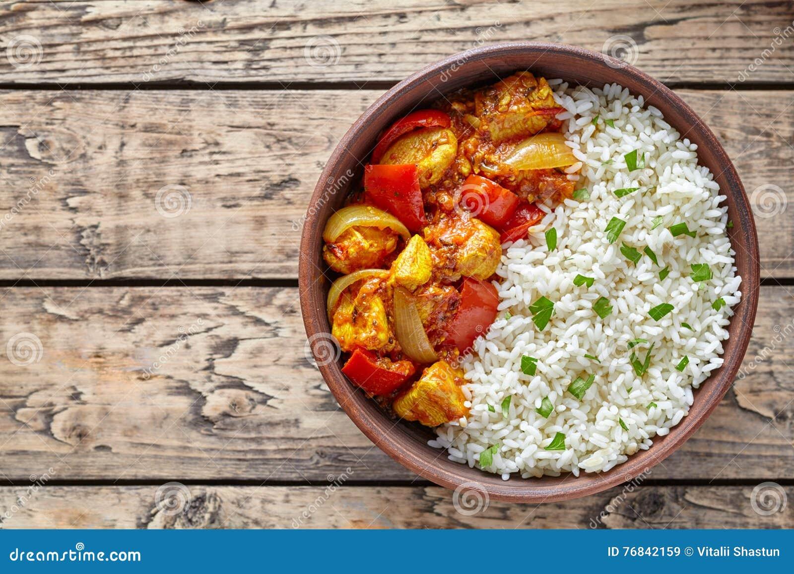 鸡jalfrezi印地安辣咖喱辣椒肉用印度大米和菜在黏土盘