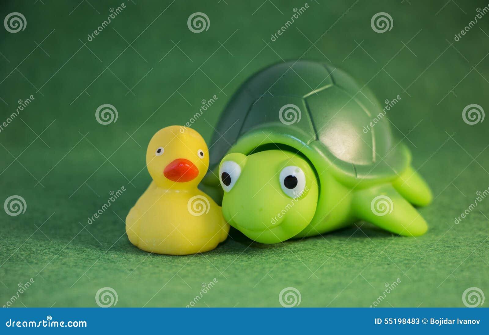 黄色摆在作为最好的朋友的鸭子和绿色橡胶乌龟婴孩玩具.图片