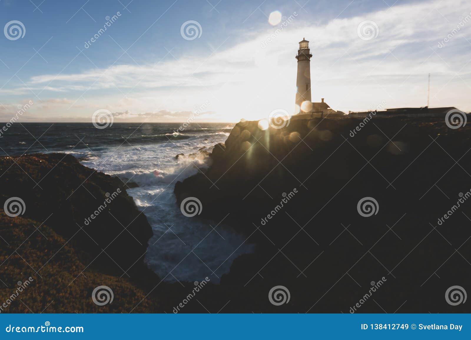 鸽子在加利福尼亚北部太平洋海岸线的点灯塔在与一片艺术性的太阳火光的日落,葡萄酒神色之前