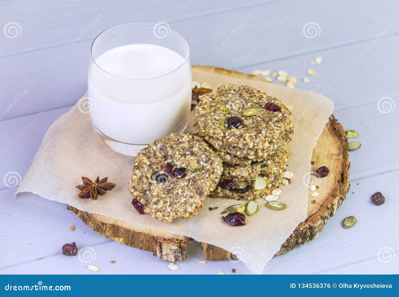 麦甜饼用干果子,种子,蔓越桔 在与一杯的木灰色背景新鲜的温暖的牛奶 舒适静物画
