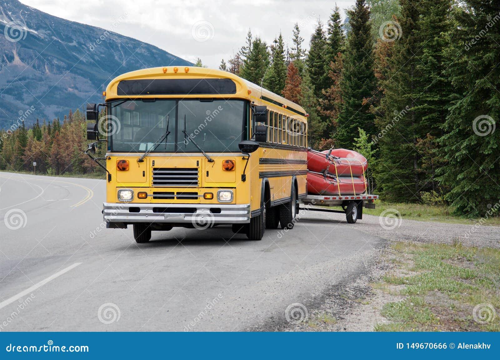 黄色公共汽车运载两条红色小船