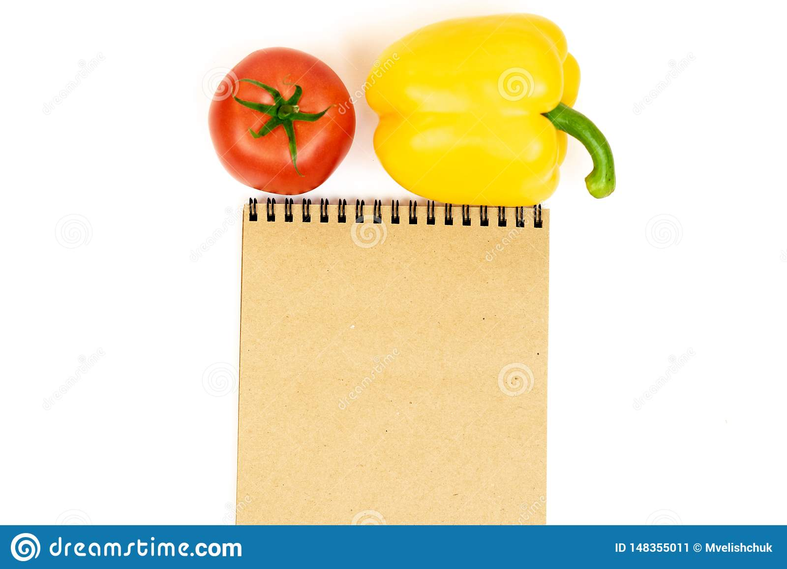 黄色喇叭花胡椒用在白色背景隔绝的蕃茄在笔记薄附近 黄色胡椒和红色蕃茄的构成在白色