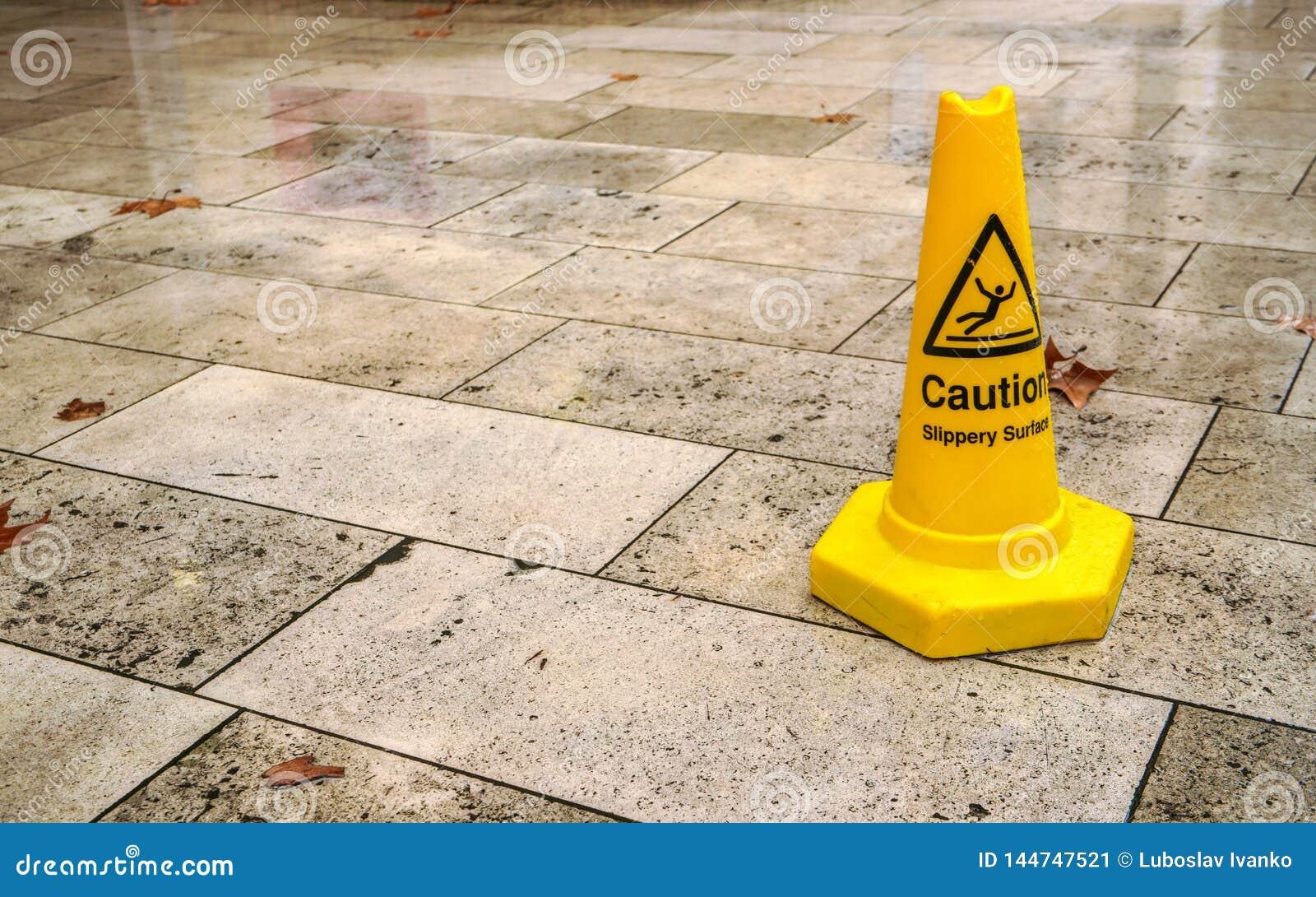 黄色小心地锥体溜滑表面标志,在湿路面瓦片