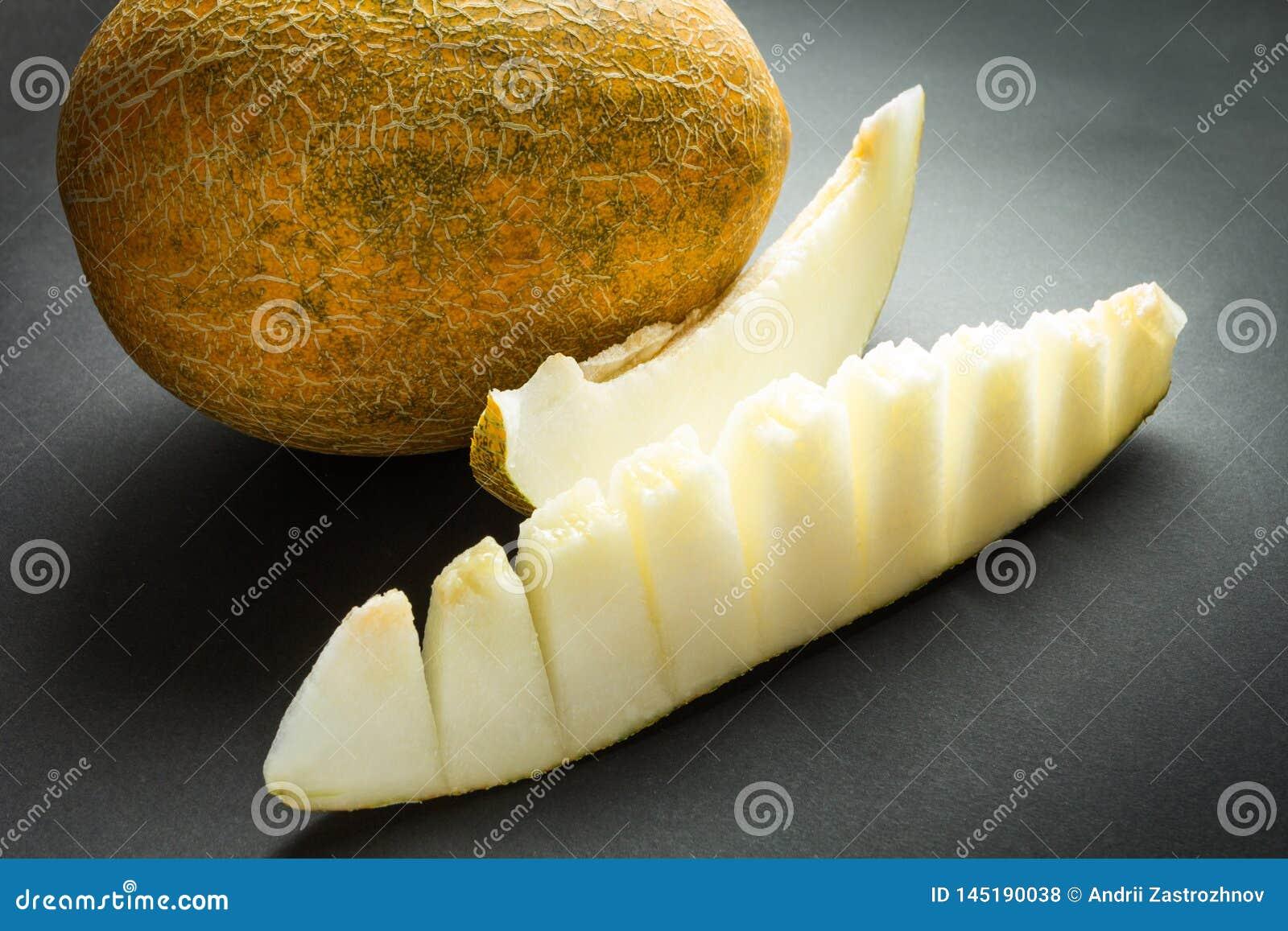 黄色有机在黑色隔绝的甜瓜瓜和切片