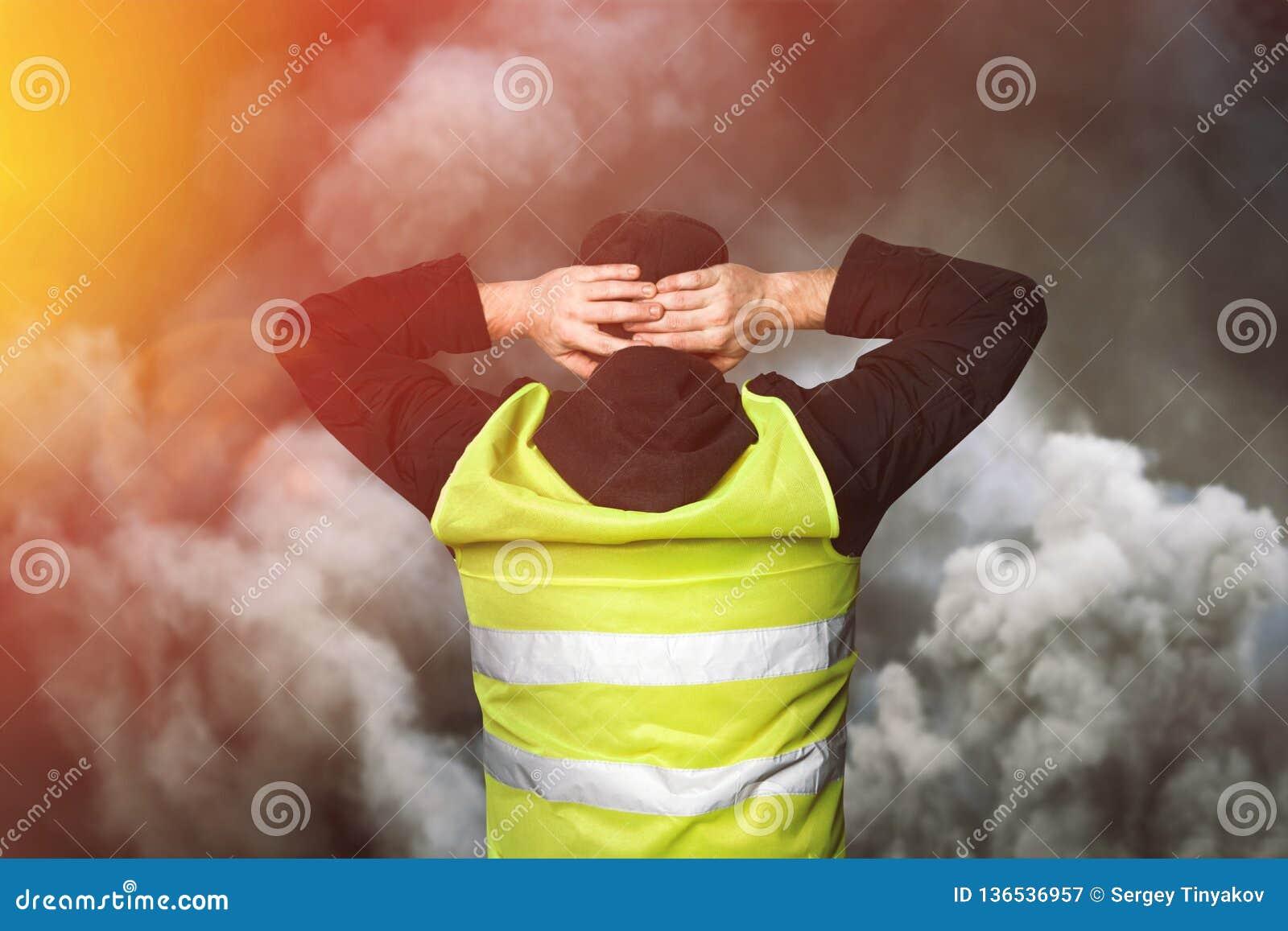 黄色背心抗议 年轻人站立与他的并且握他的在他的头的手作为守纪的标志在催泪弹的