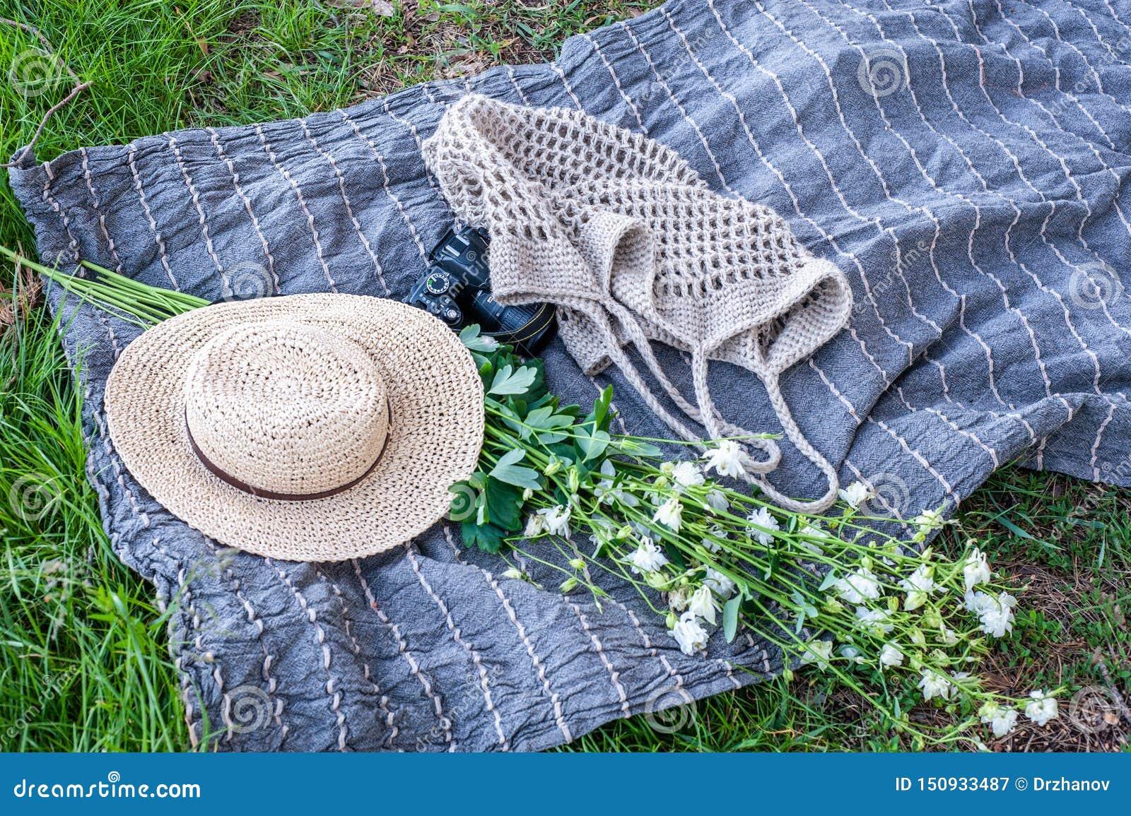 黄色草帽、花花束、照相机和被编织的袋子在室外的草的灰色海滩席子,等轴测图放置