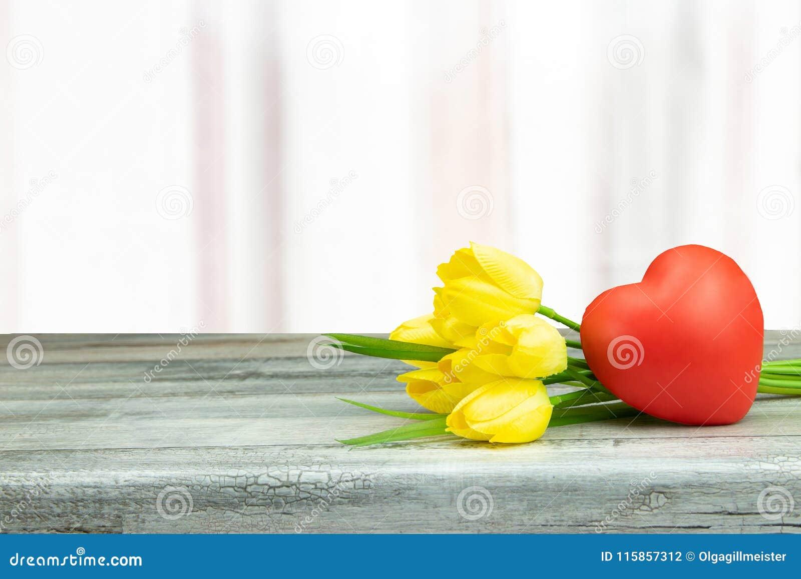 黄色郁金香的装饰构成和在rusti的红色心脏