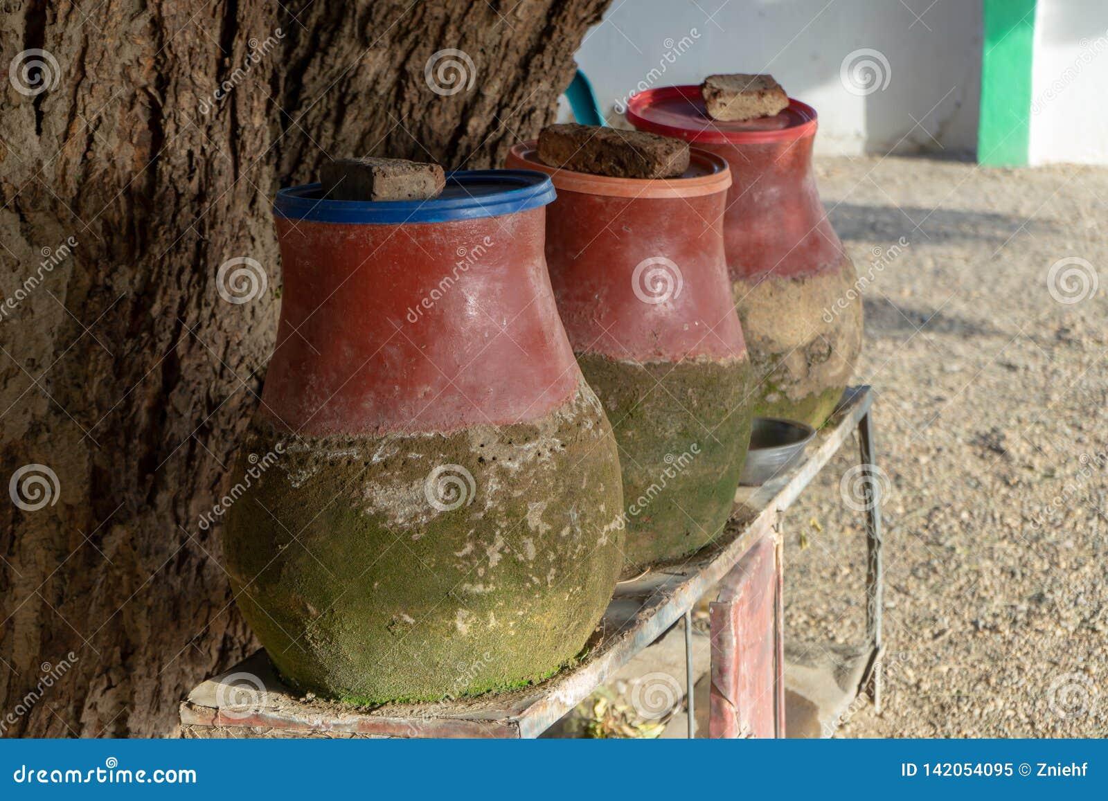 黏土水罐充满水为徒步旅行者和访客喝或洗涤在一个村庄在苏丹