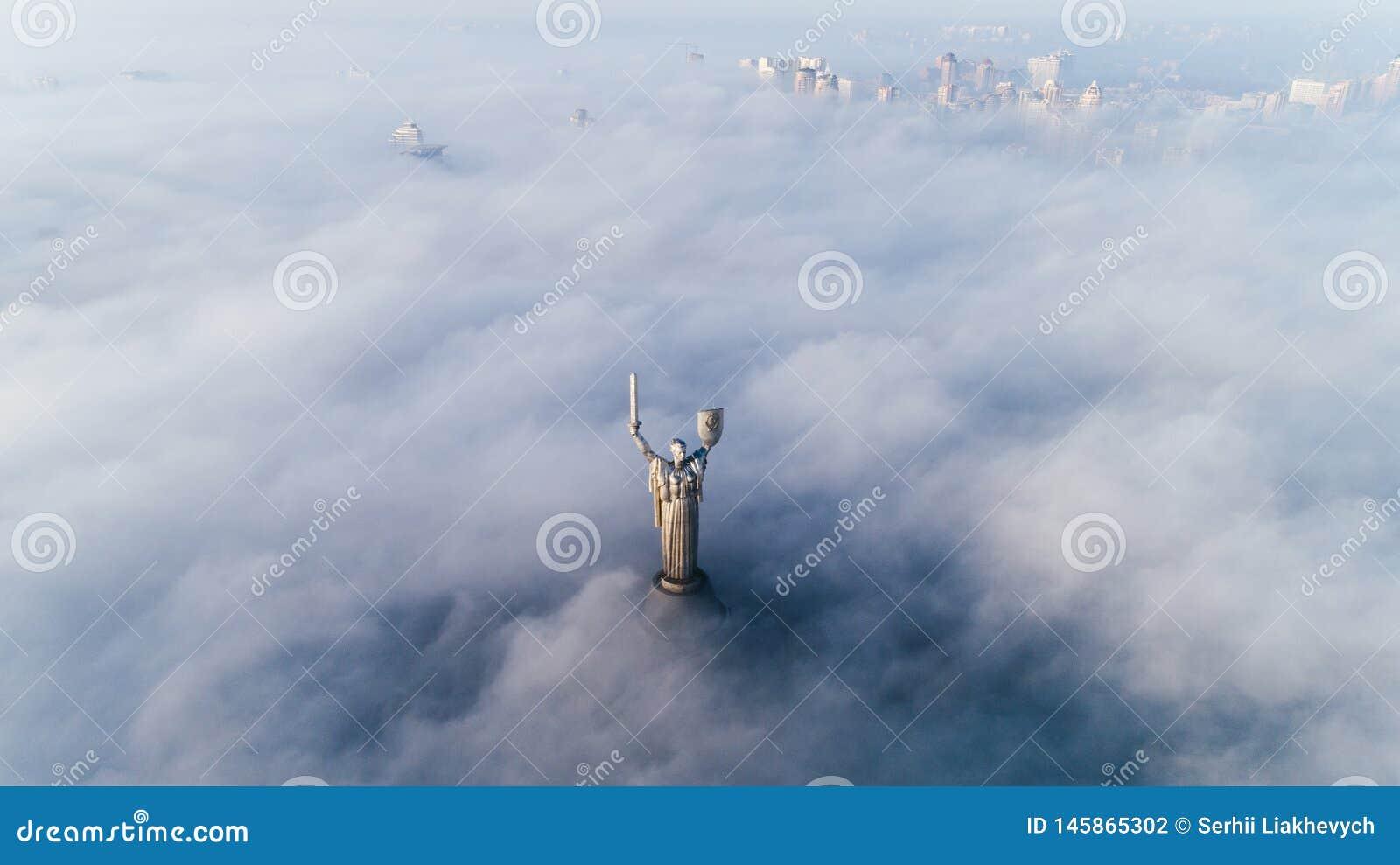 黏附在他们外面的秋天雾和祖国纪念碑厚实的云彩