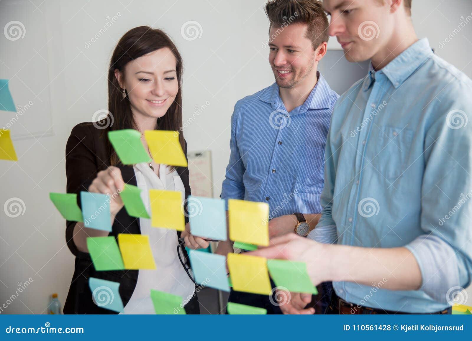 黏附笔记的企业专家在玻璃在办公室