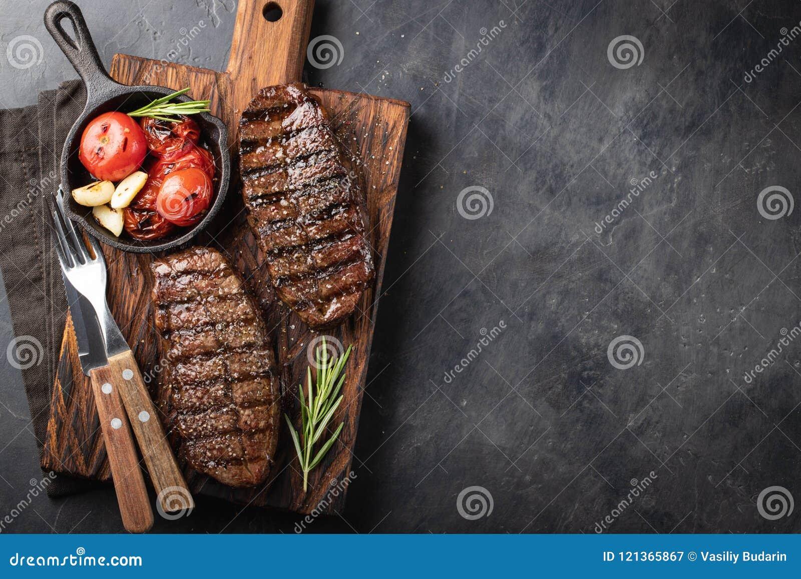 黑人安格斯特写镜头立即可食的牛排上面刀片牛肉品种用格栅蕃茄,大蒜和一个木板的 的treadled