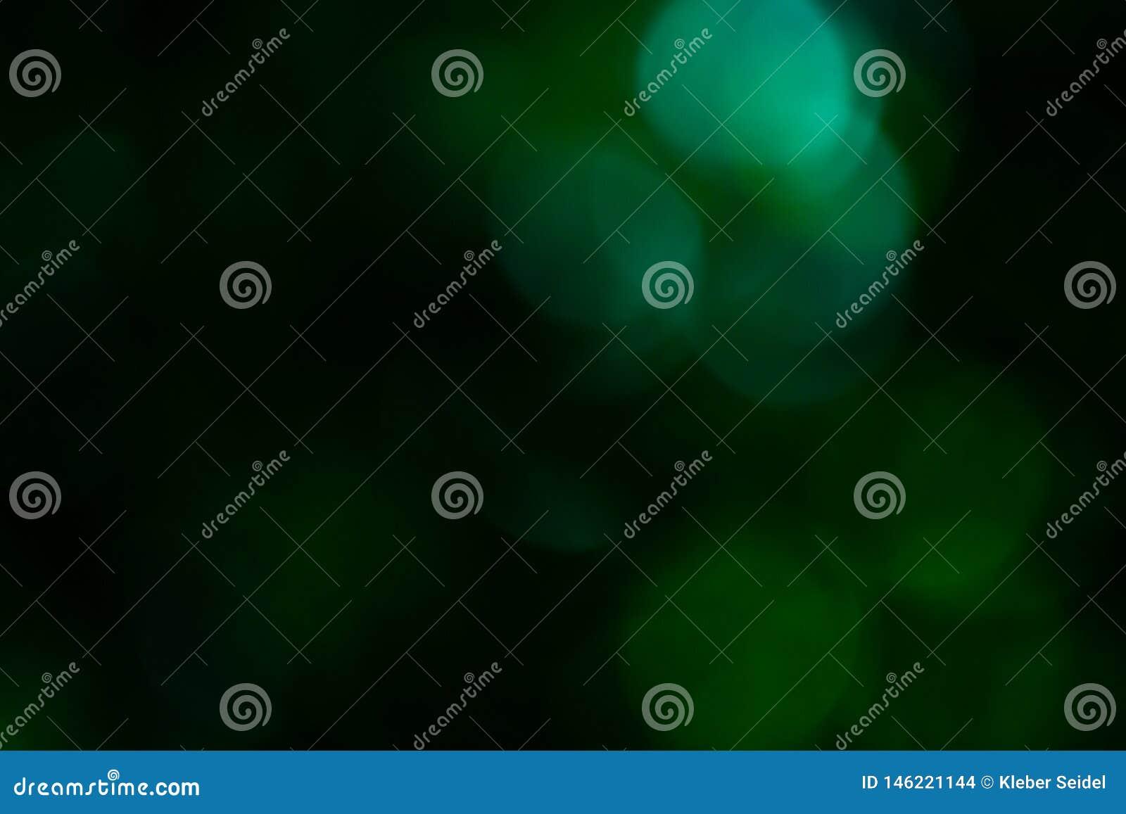 黑和绿色bokeh被弄脏在焦点,defocused抽象圆背景外面
