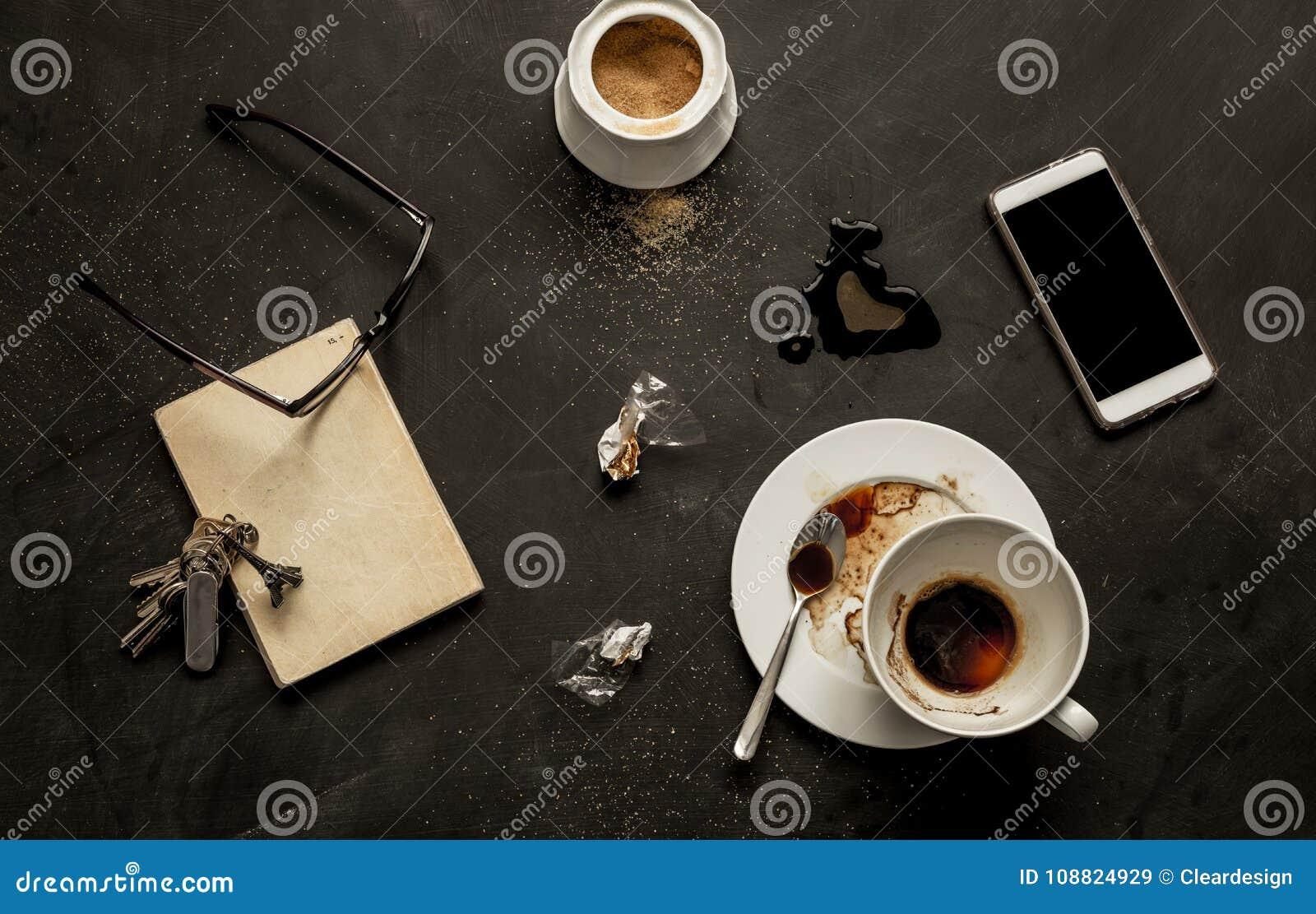 黑咖啡馆桌-空的咖啡杯和智能手机