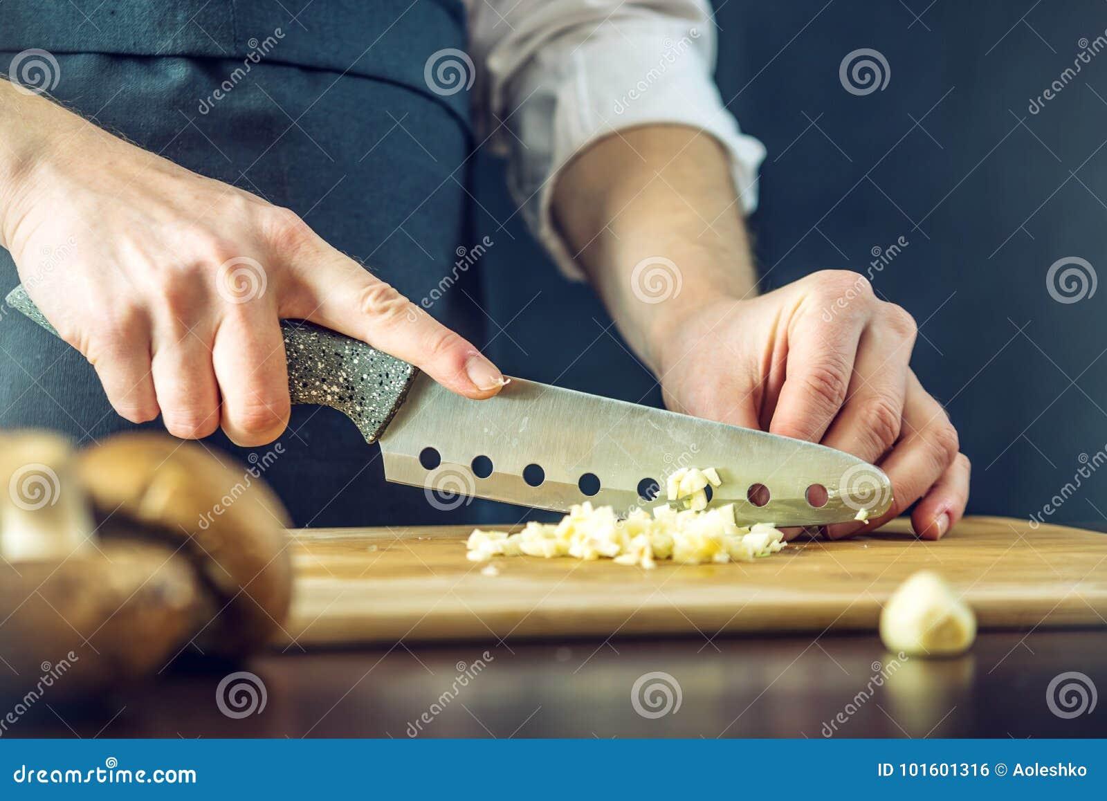 黑围裙的厨师切与刀子的大蒜 环境友好的产品的概念烹调的