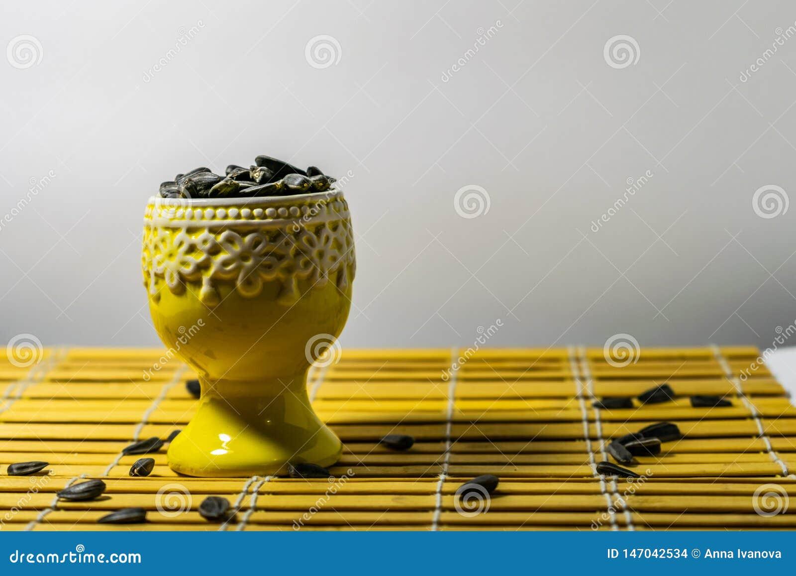 黑小向日葵种子 点击与果壳的种子 在一个黄色微型立场的极少数在一块木餐巾 溢出了有些种子