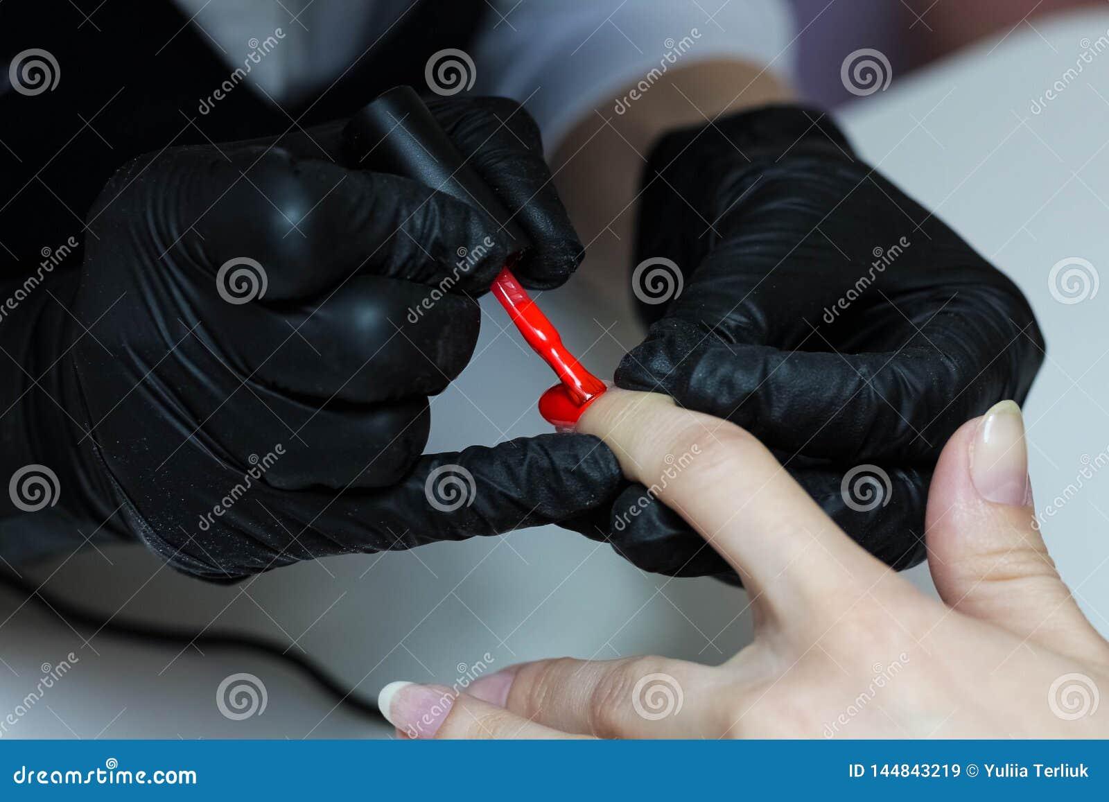 黑手套关心的修指甲专家关于手钉子 修指甲师绘与红色指甲油的钉子
