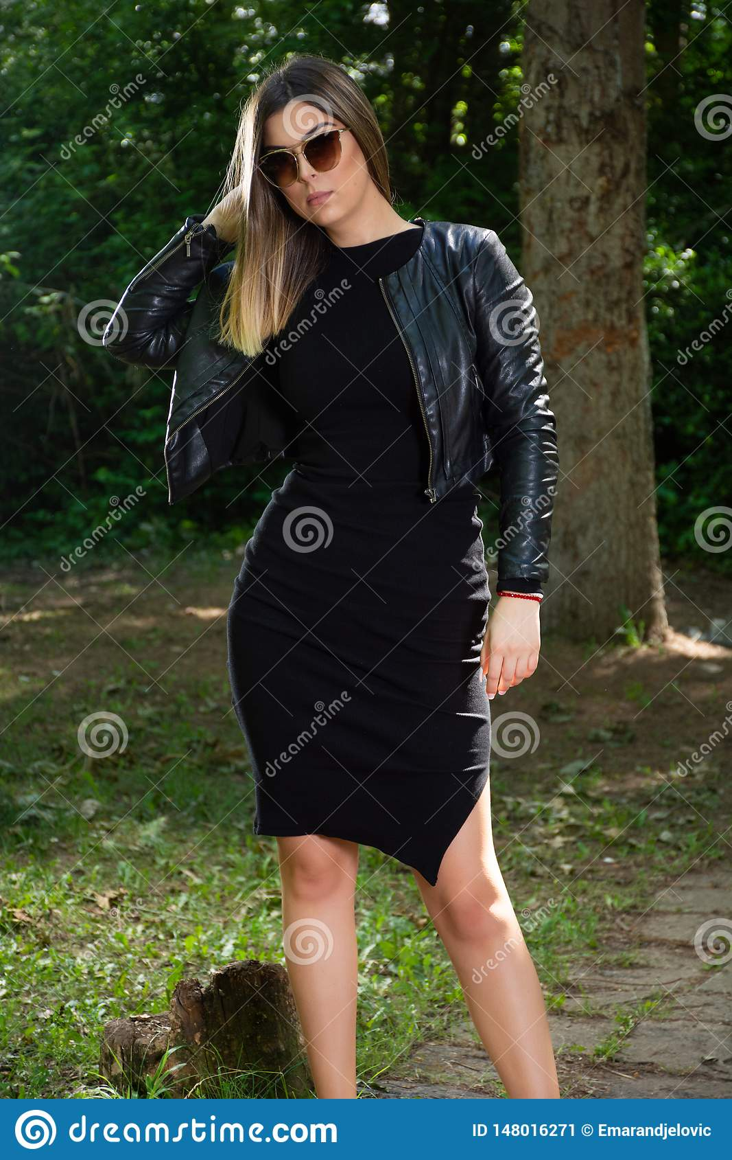 黑摆在本质上的礼服的一名美丽的时装模特儿妇女和皮夹克和太阳镜在一个晴朗的春日