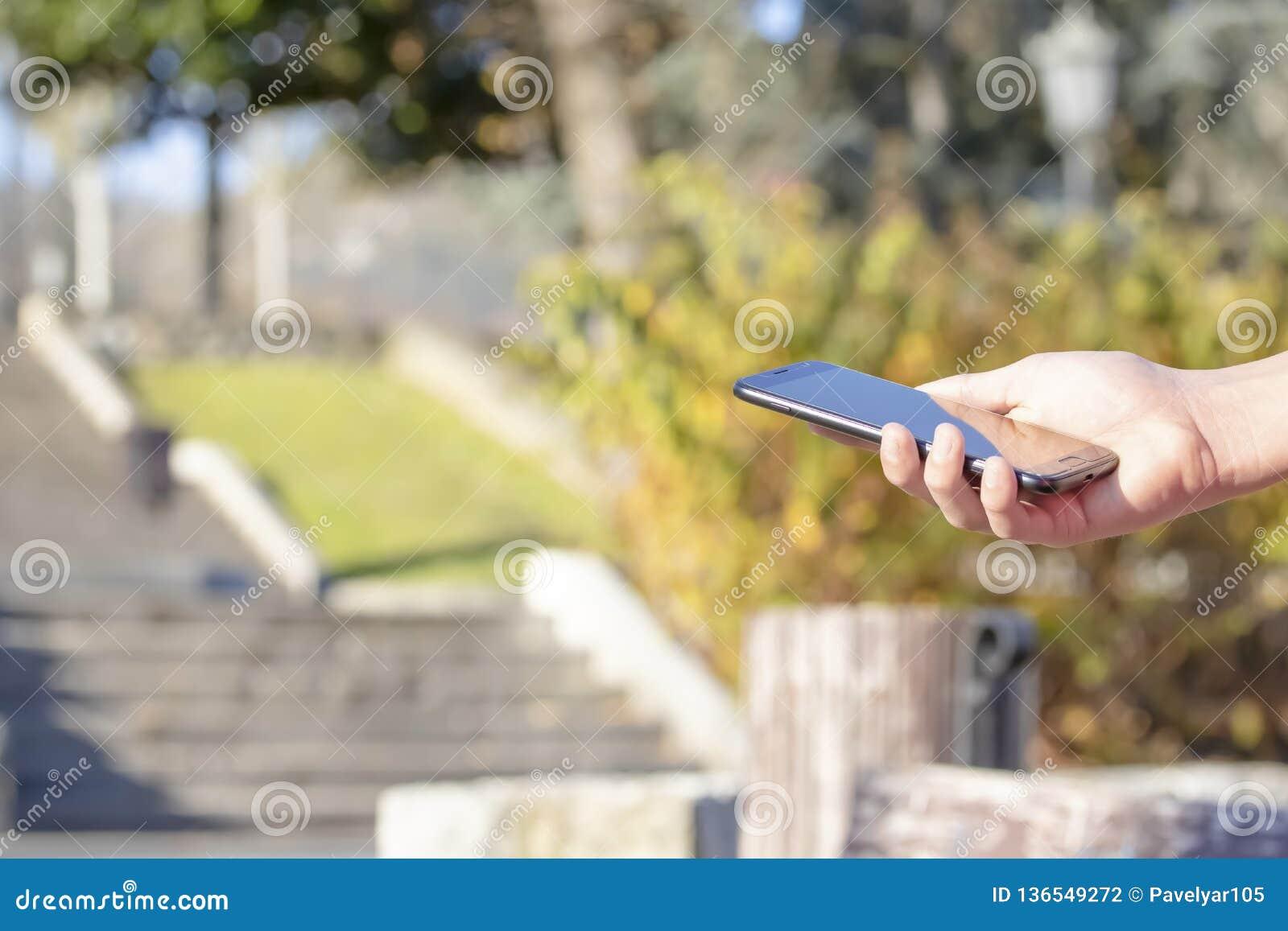 黑智能手机在手中在露天公园,点燃由太阳
