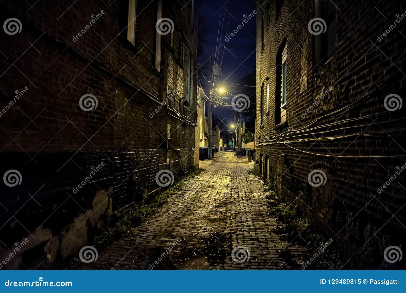 黑暗和令人毛骨悚然的都市城市鹅卵石砖胡同在晚上