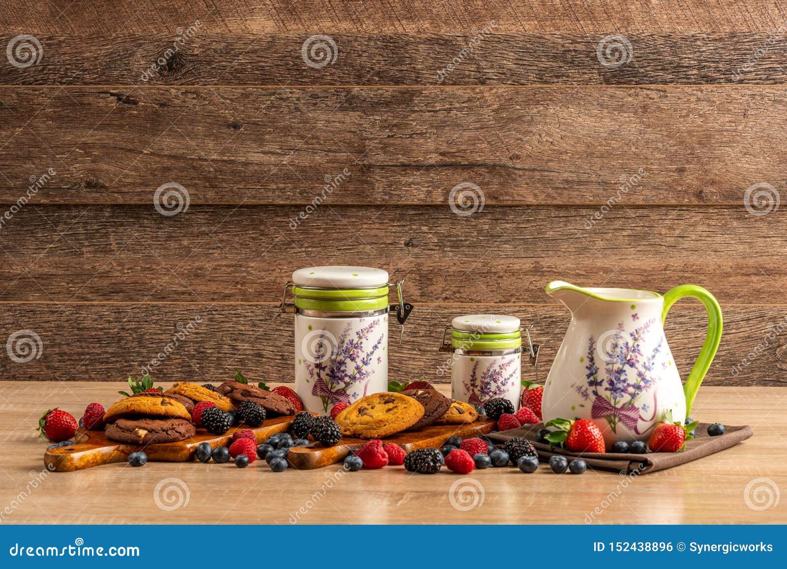 黑暗的巧克力饼干用新鲜的森林果子和陶瓷船在木桌上