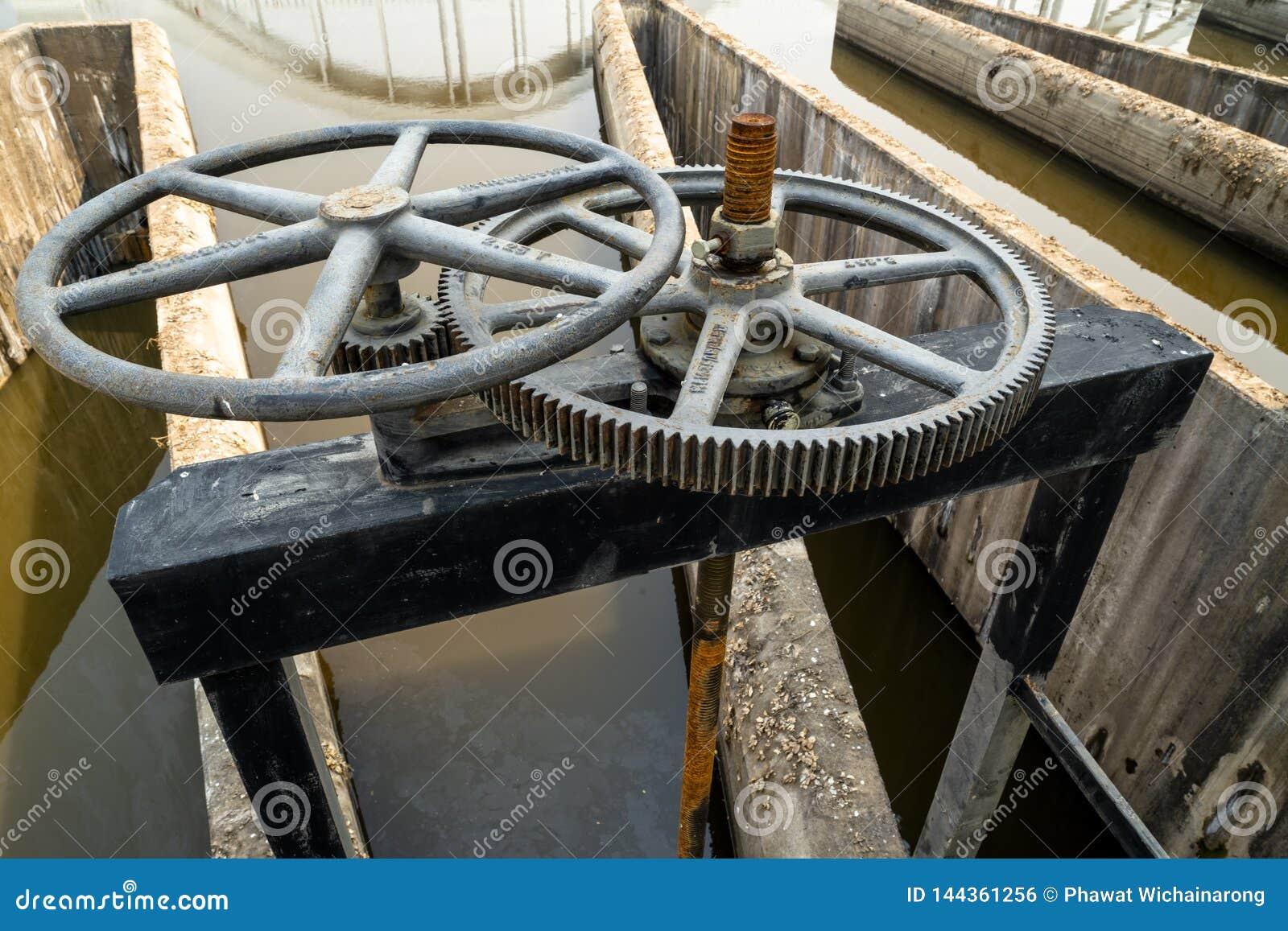黑有文本的金属钝齿轮控制水闸特写镜头在泰语意思'物产'在一边