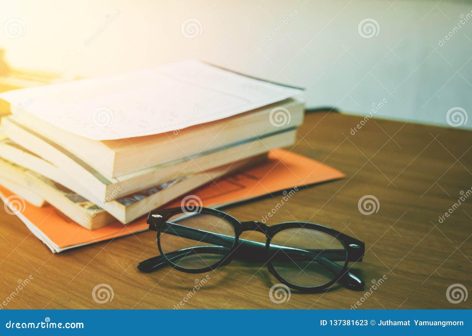 黑玻璃和书在图书馆里学会堆,在桌上,大学有日落背景 登记概念教育查出的老