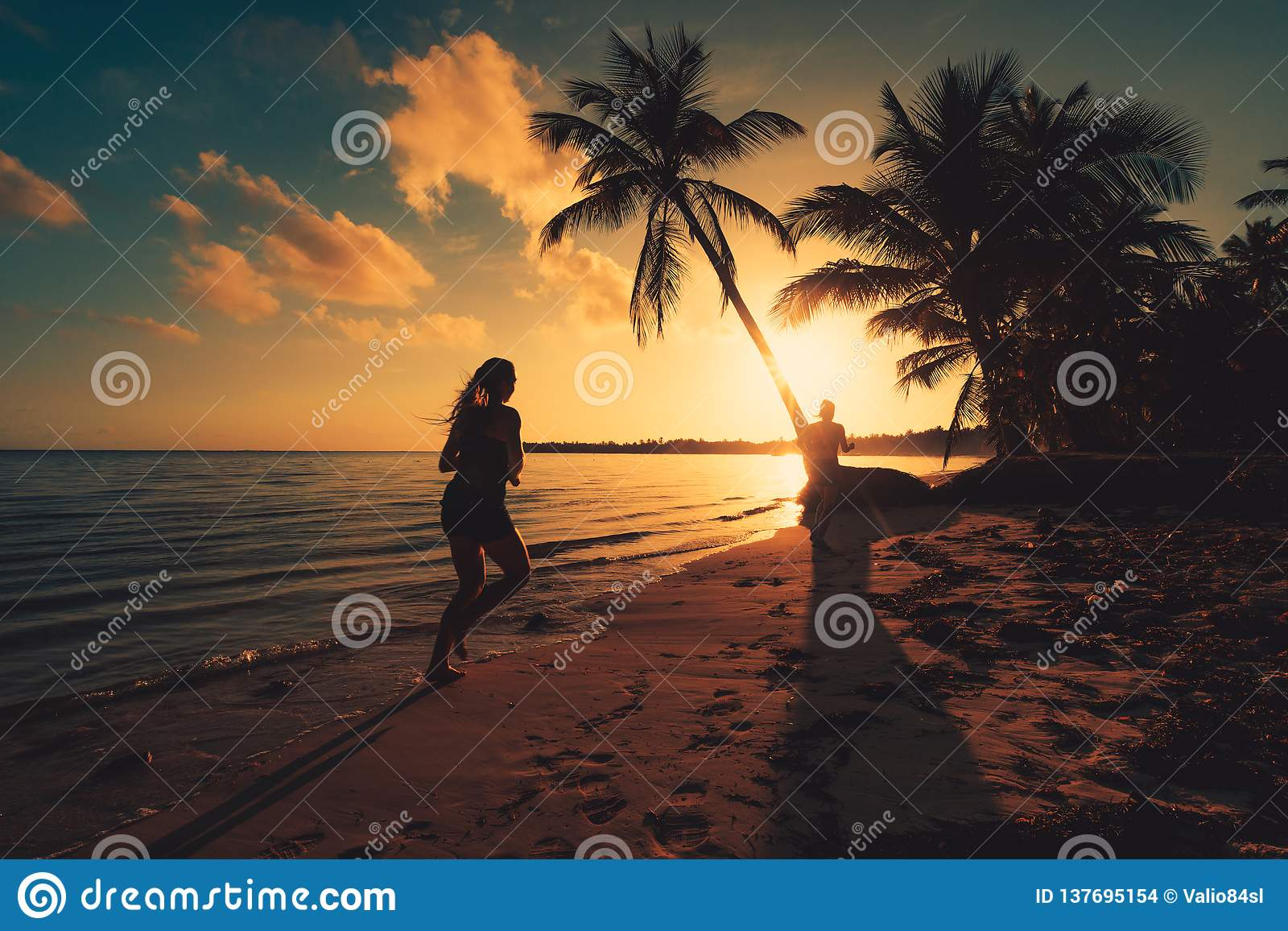 黑色克里米亚dag kara山海运日出视图 在热带海岛海滩蓬塔卡纳的女孩赛跑