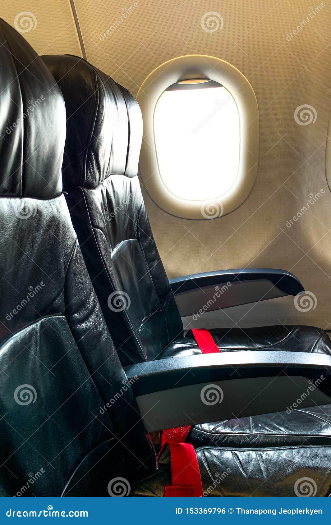 黑飞机位子 红色游乐器具和窗口在客舱经济舱