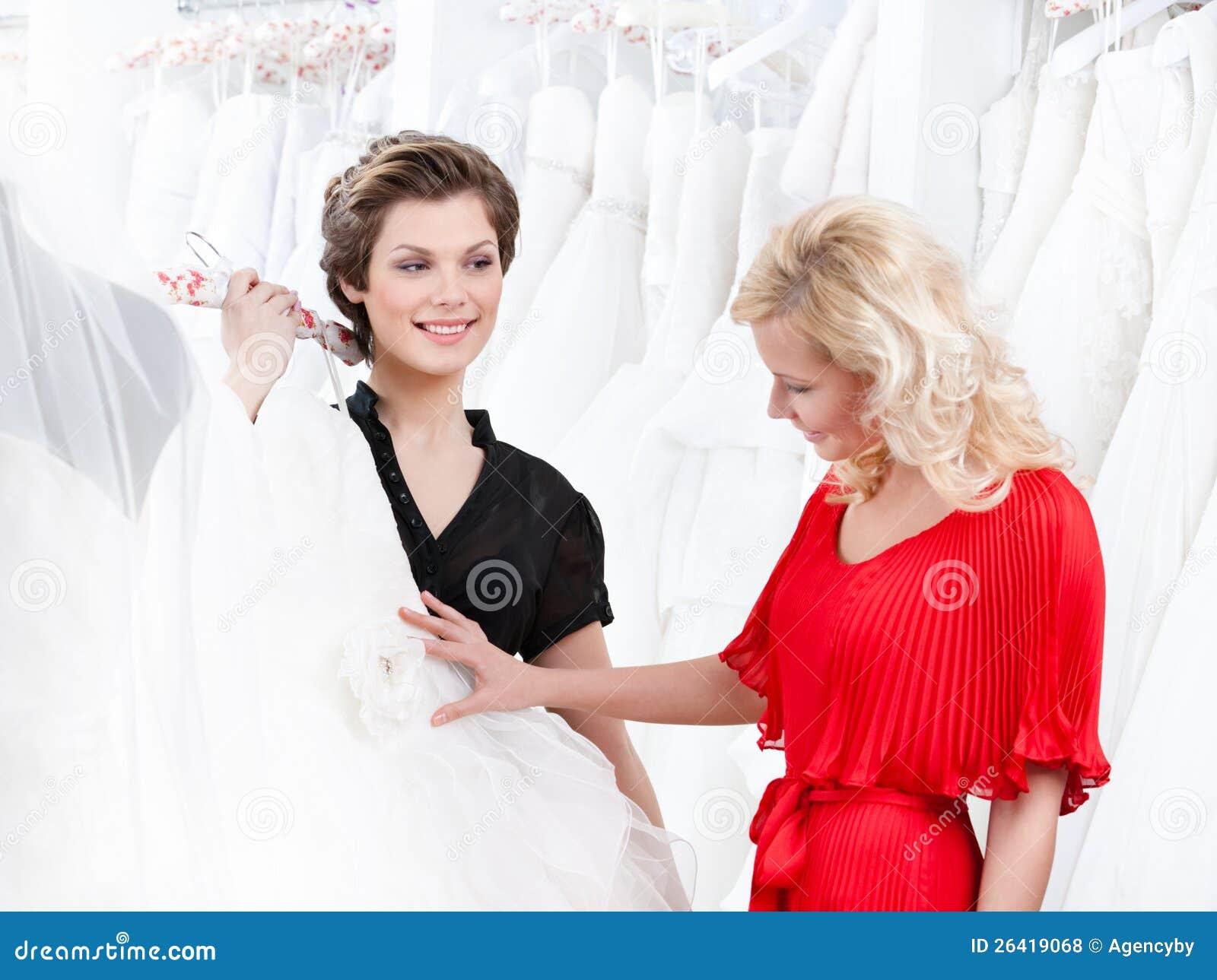 2 девушки имеют хороший взгляд на платье венчания