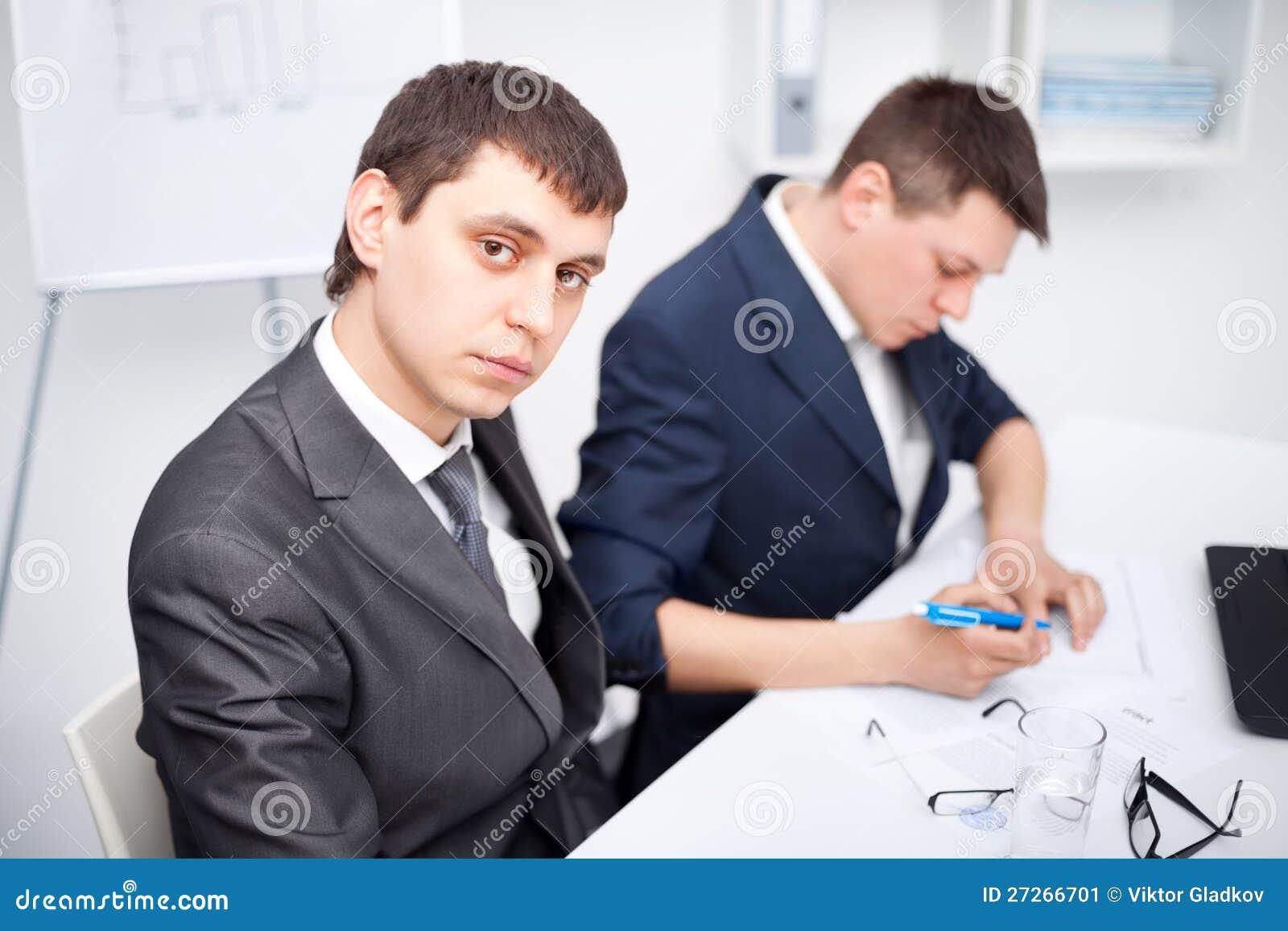 2 молодых бизнесмена работая в офисе