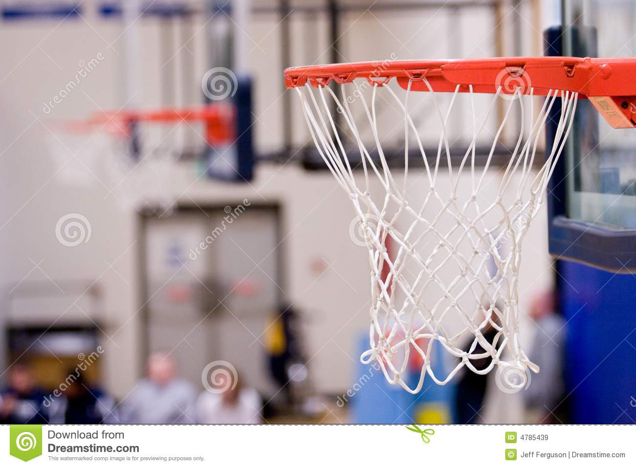 3 Basketball Hoops with nets hanging inside a gym