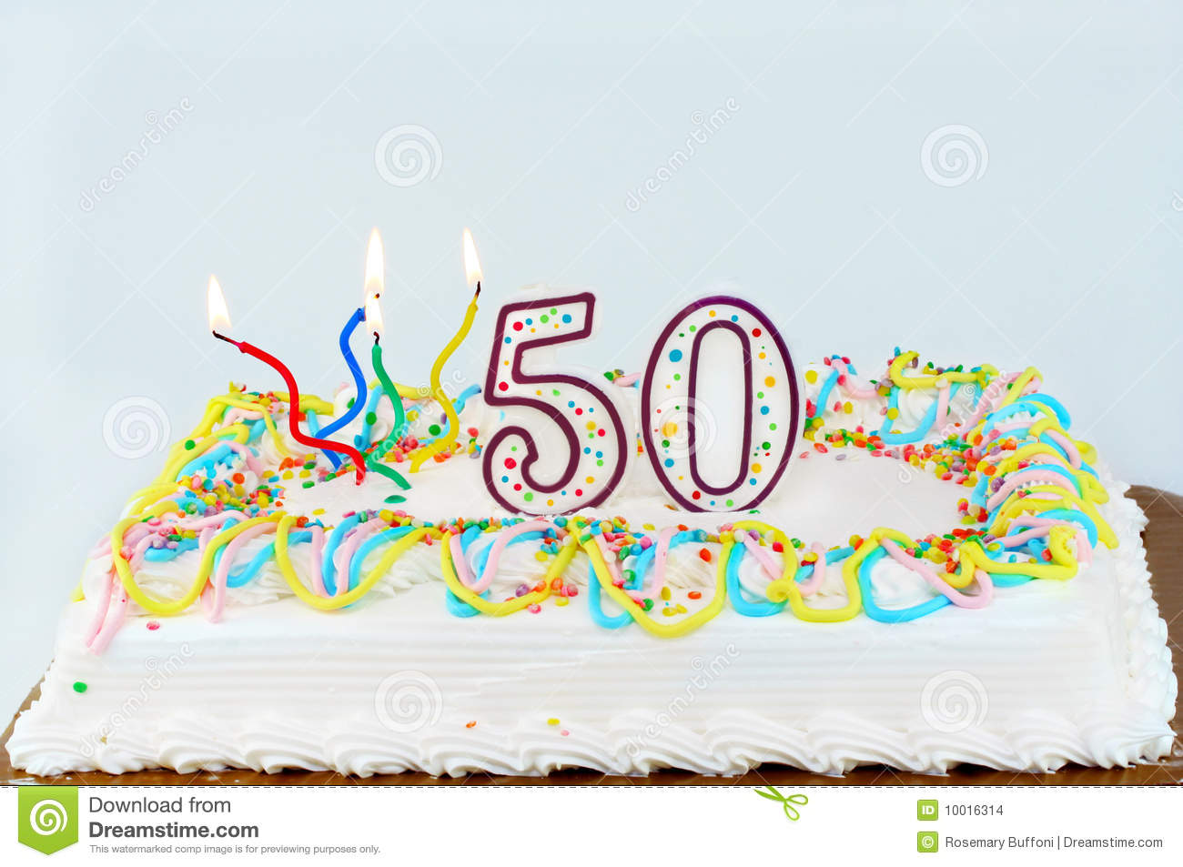 White frosted birthday cake with lit candles and the number 50 on top