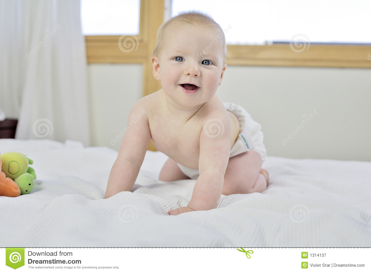 Month old baby boy starting to think about crawling with 1st teeth