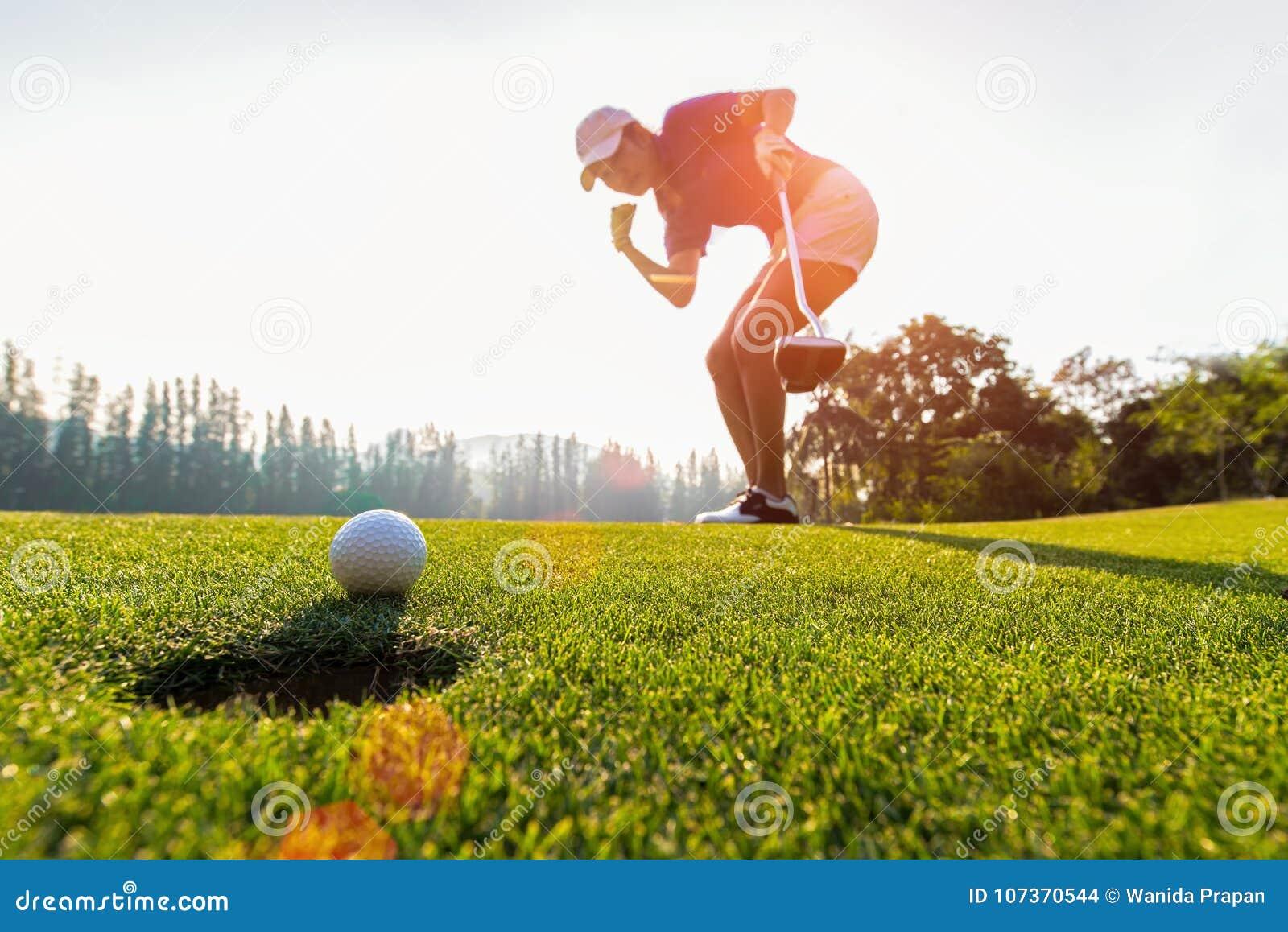 Ação asiática do jogador de golfe da mulher a ganhar após a bola de golfe de colocação longa no golfe verde, tempo do por do sol,