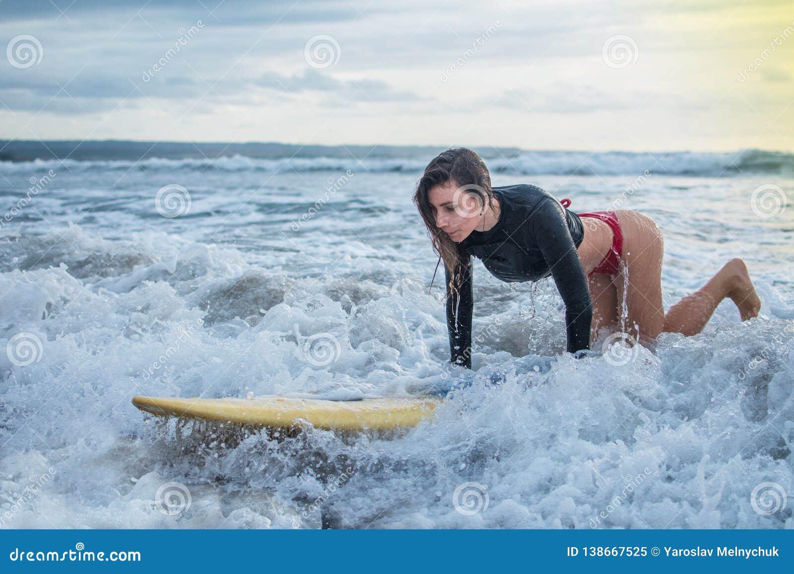 A ação da jovem mulher tenta pisar estando na prancha no MED do oceano, montando no treinamento de habilidade do attemption da on