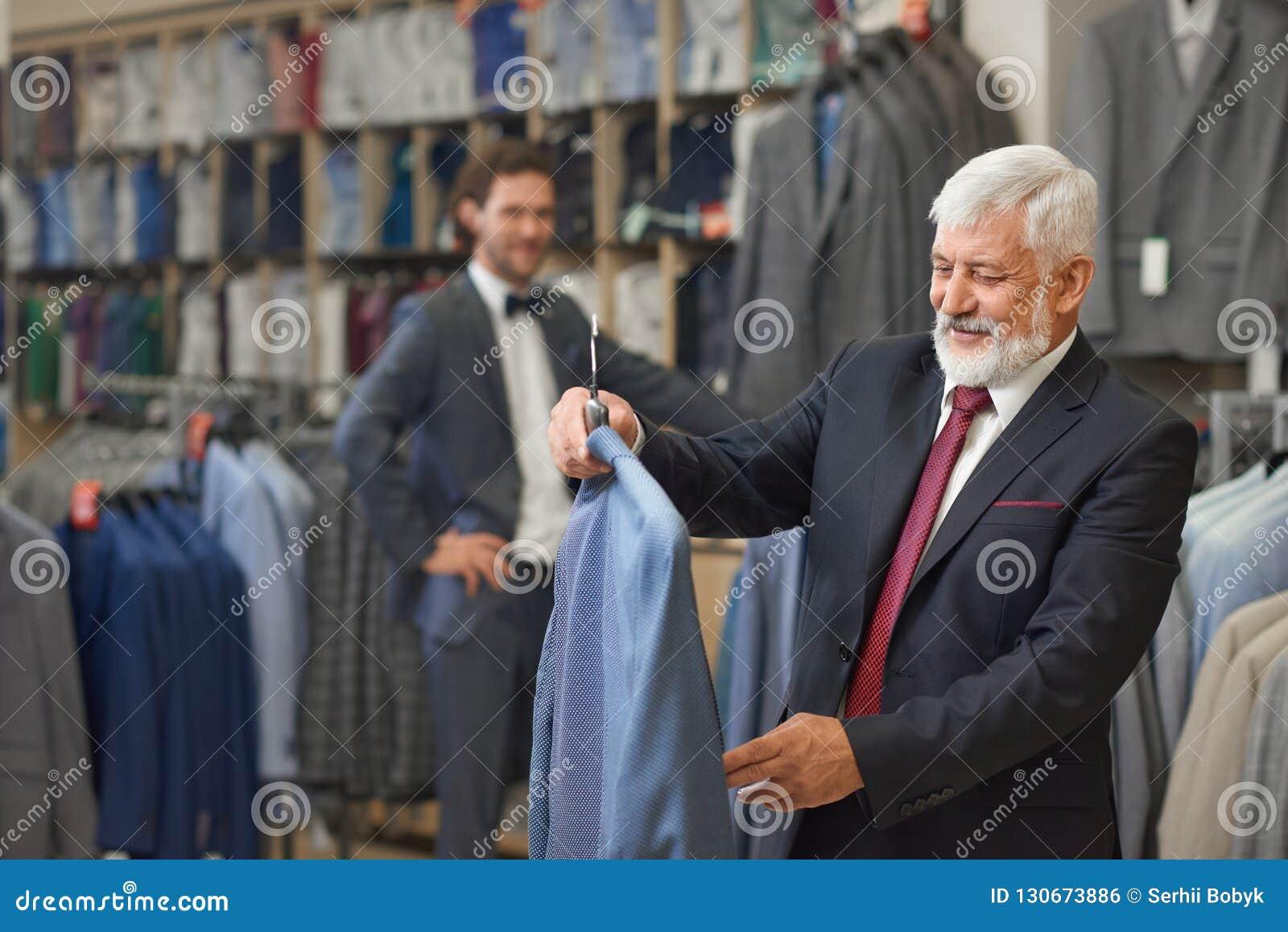 Aîné bel avec les cheveux gris choisissant les vêtements élégants