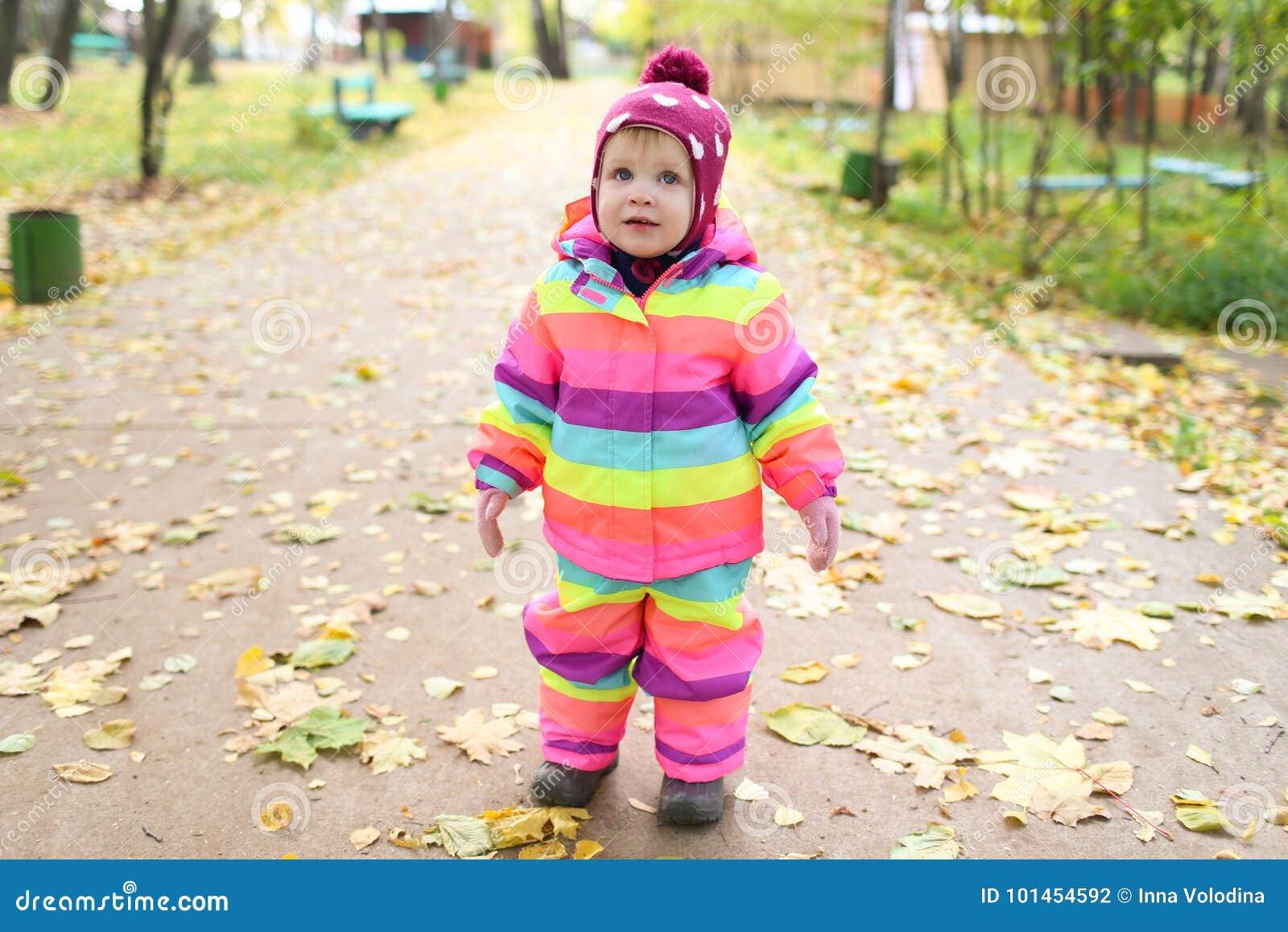 1 año felices de niña que camina en otoño
