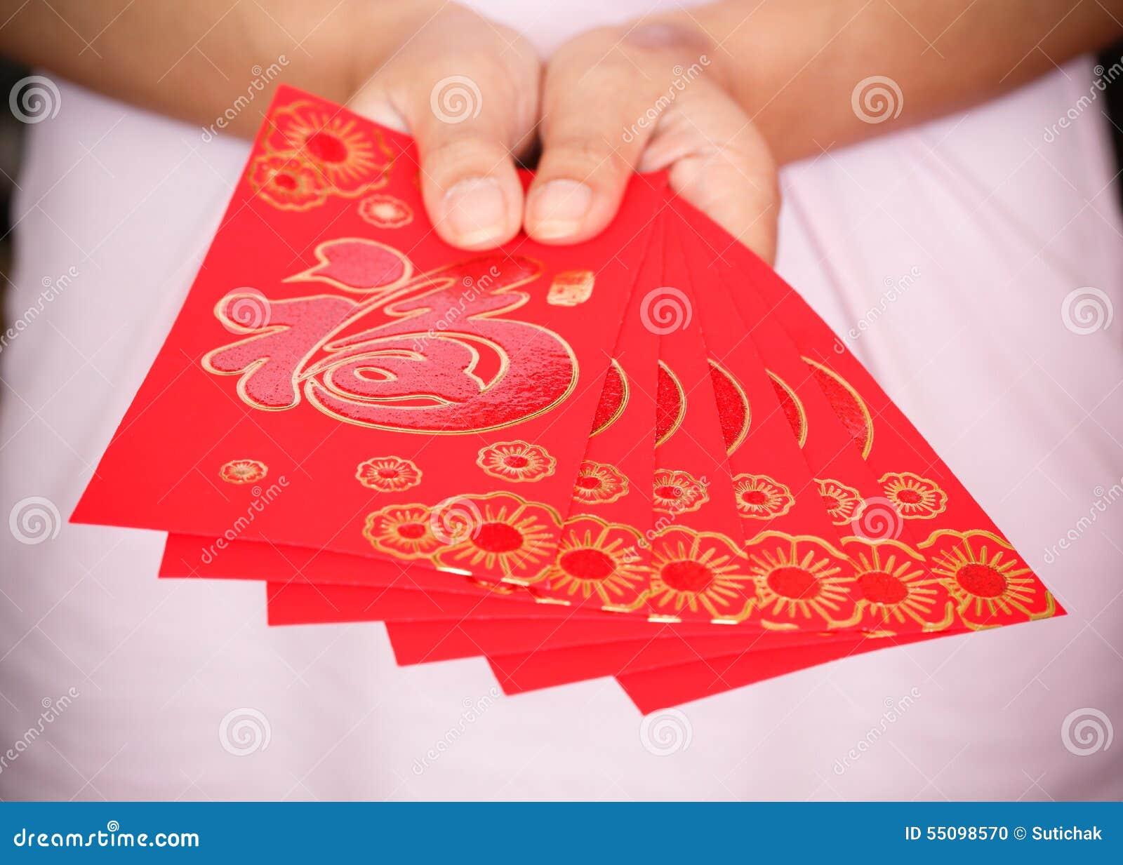 Año Nuevo chino feliz, mano de la mujer que sostiene el sobre rojo