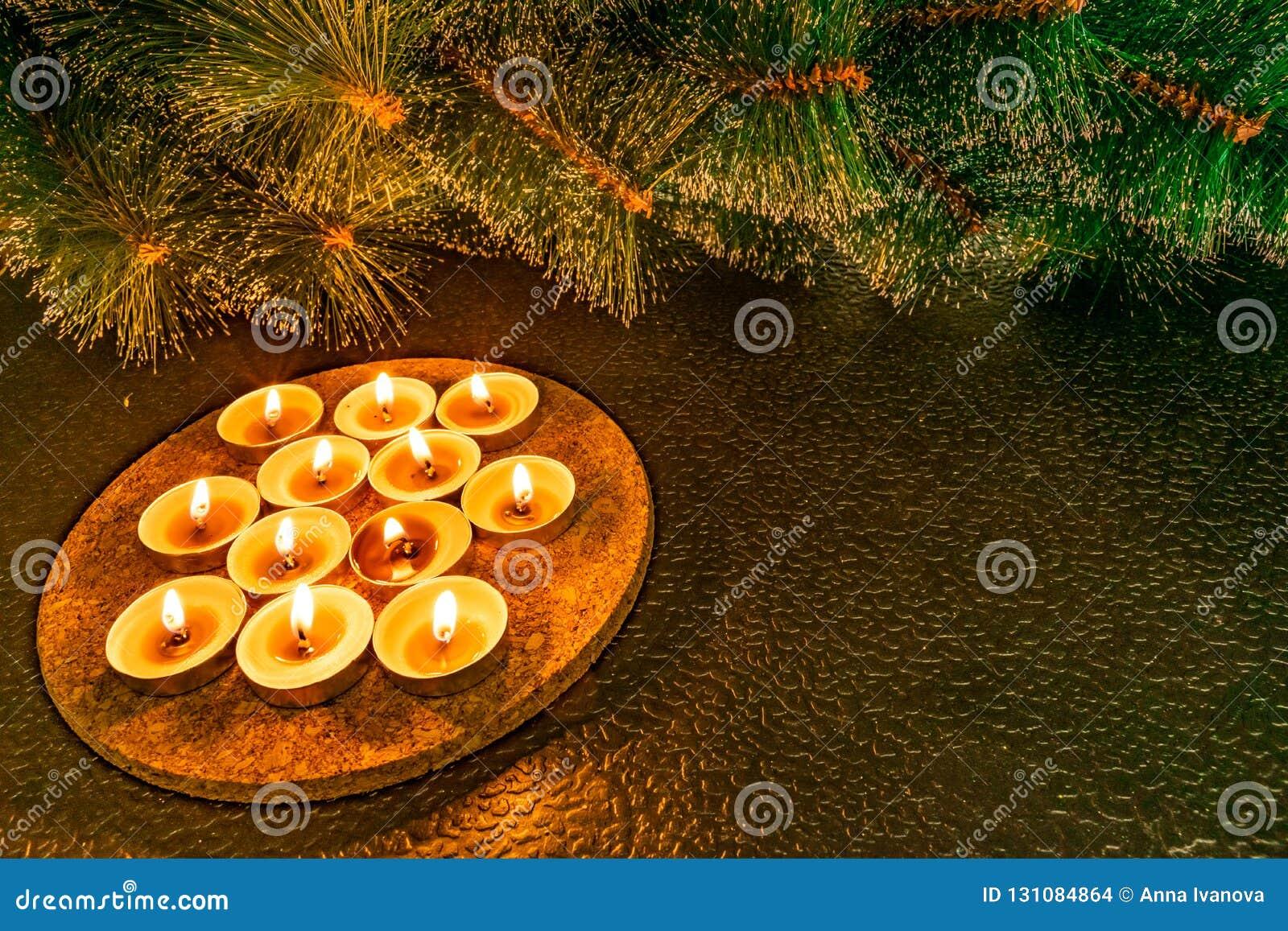 Año Nuevo y la Navidad, pino artificial verde en un fondo negro teniendo en cuenta velas de la cera Tactos acogedores calientes a