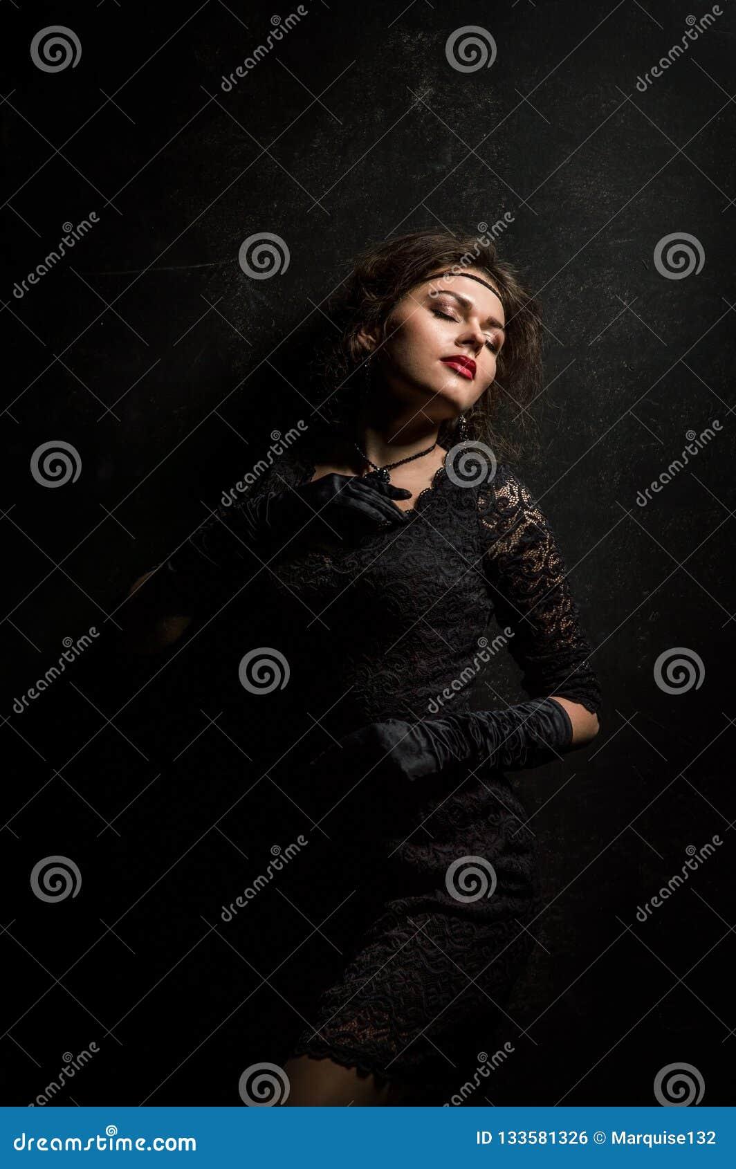 Años 20 del rugido Mirada de la cámara Una mujer joven hermosa en un vestido negro del cordón está tocando la joyería en su cuell