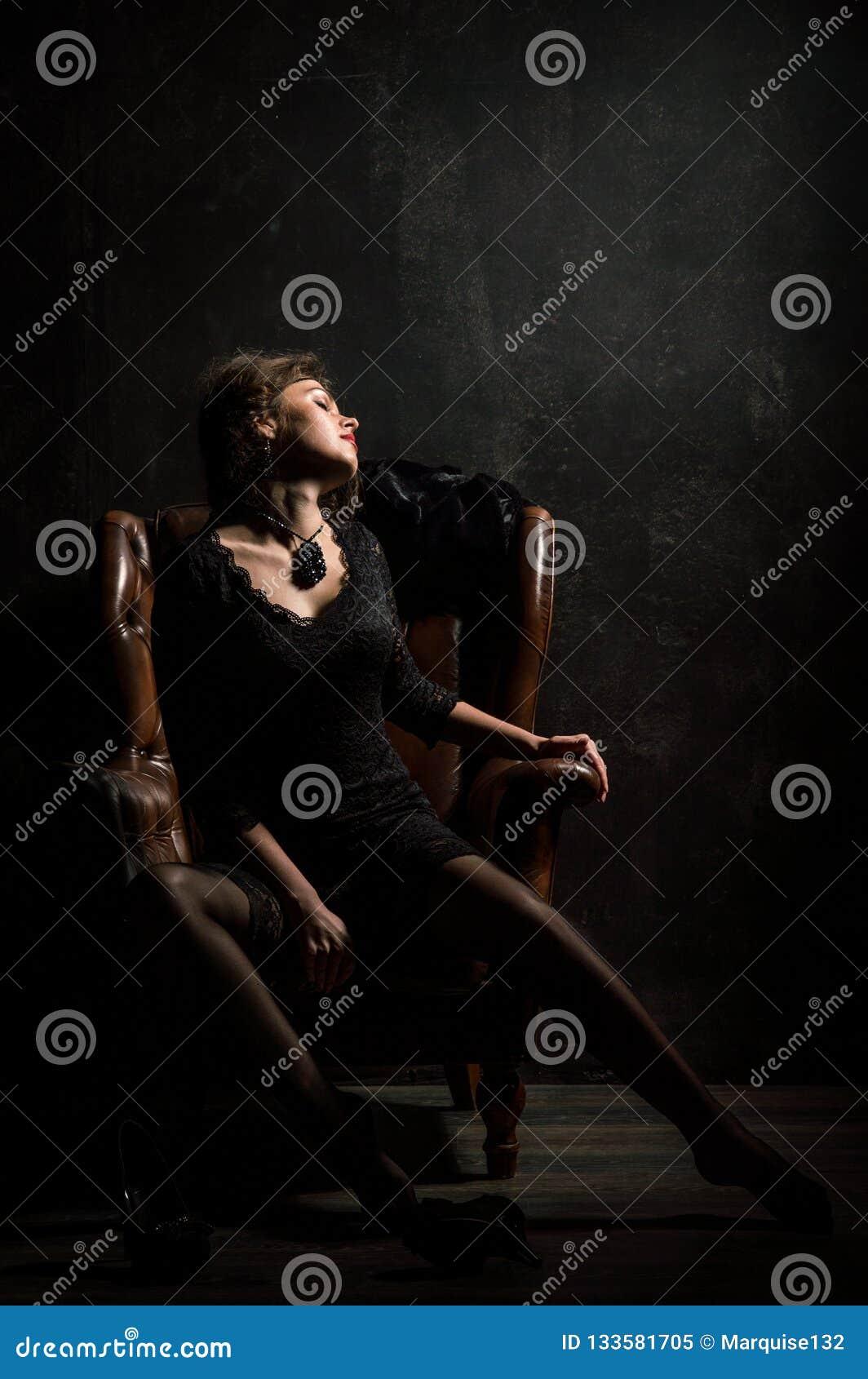 Años 20 del rugido Mirada de la cámara Una mujer joven hermosa en un vestido negro del cordón sensual se está sentando en una sil