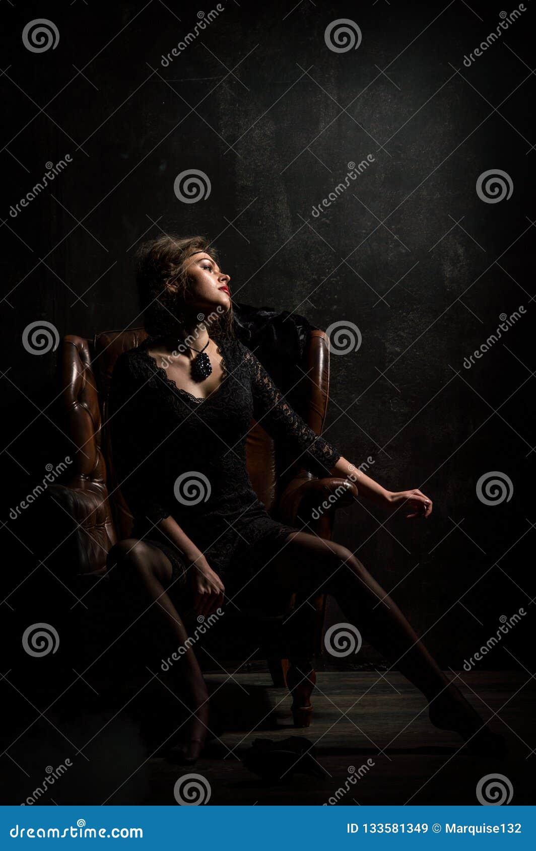 Años 20 del rugido Retrato de la mujer en el estilo de Gatsby Mirada de la cámara Una mujer joven hermosa en un vestido negro del