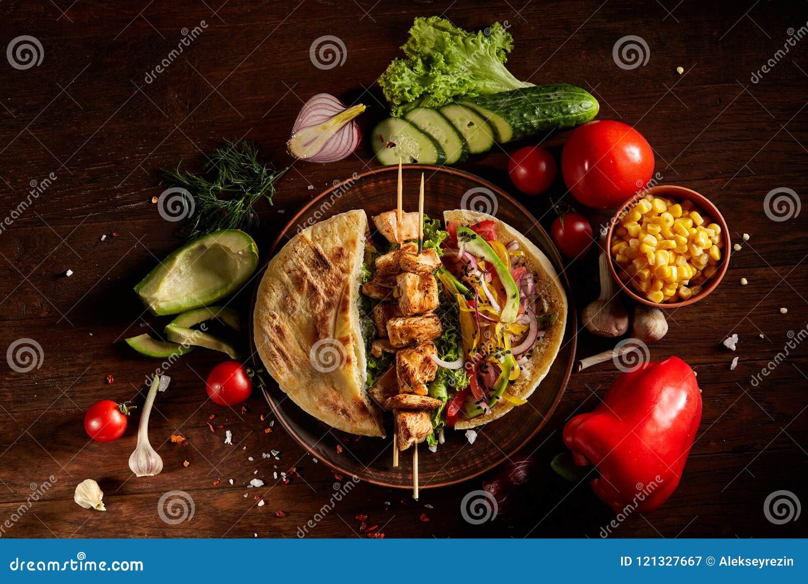 Aún slife exótico con la pita, las verduras frescas y kebab sobre el fondo de madera, foco selectivo