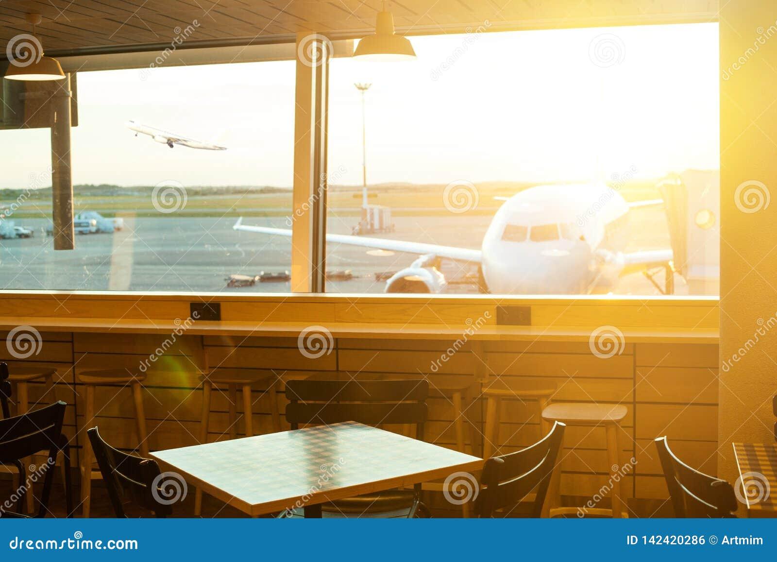 Aairport utanför fönsterplatsen som väntar på flyget Parkerat flygplan på flygplats till och med portfönstret