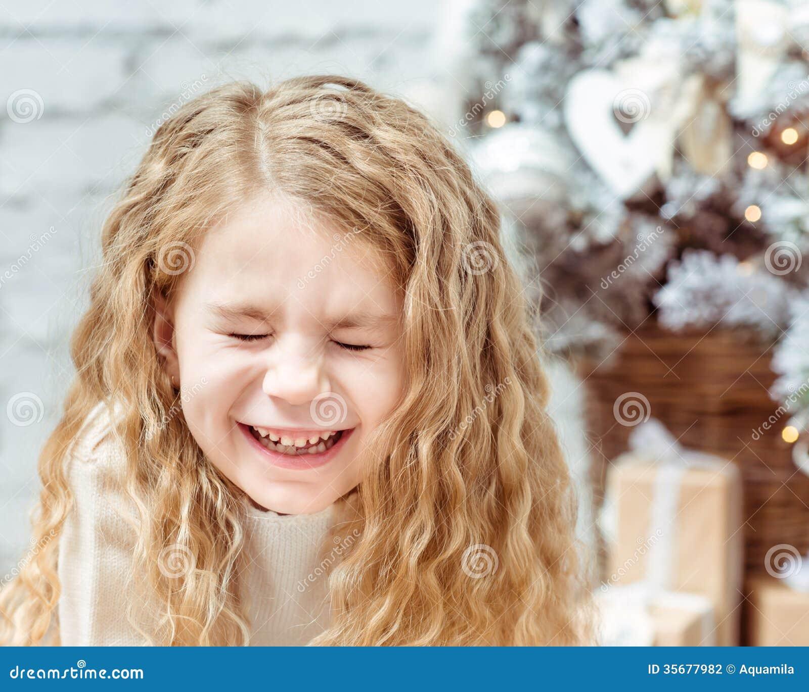 Aanbiddelijk blond meisje die met gesloten ogen, Kerstmis lachen