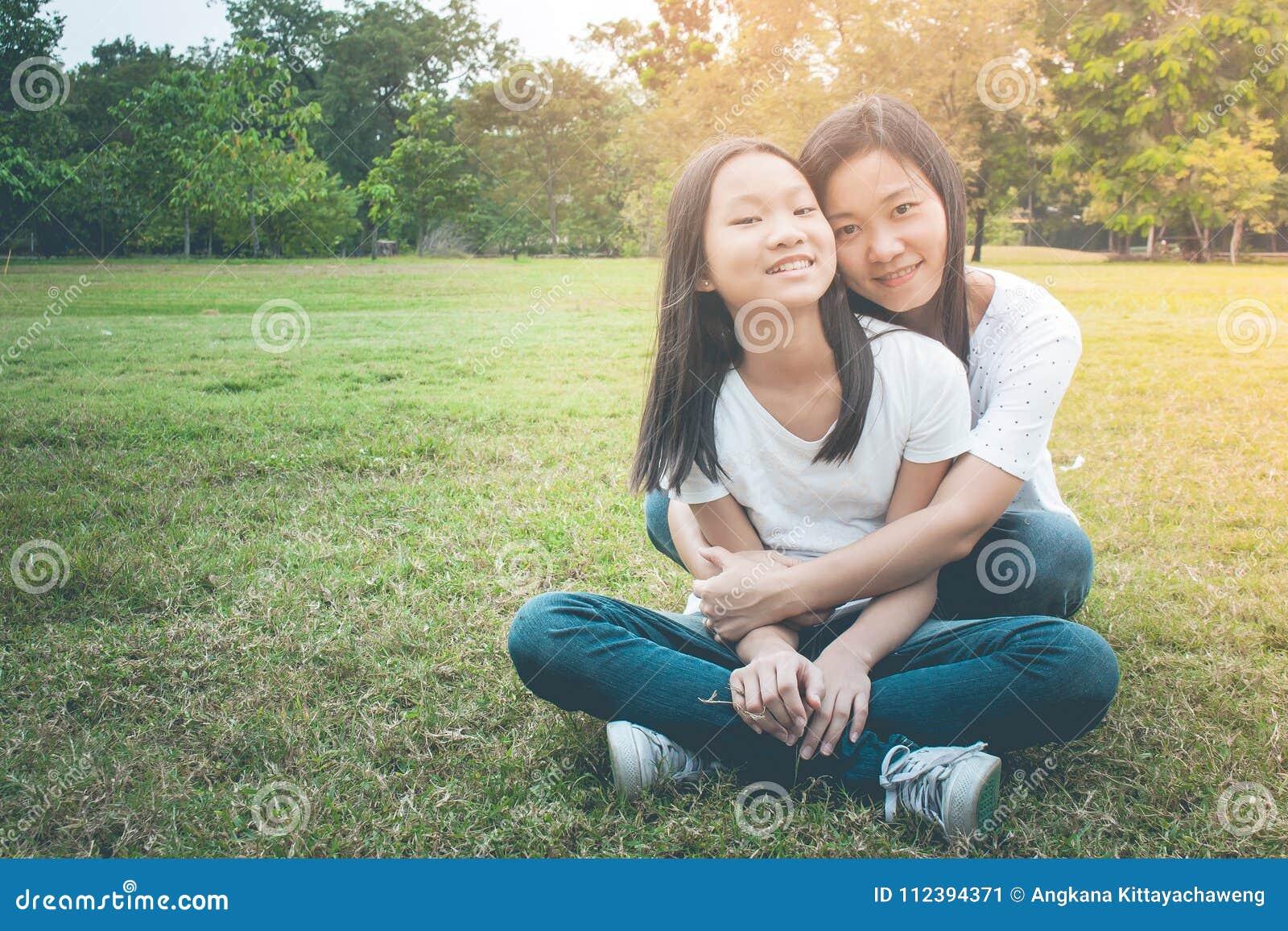 Aanbiddelijk en Familieconcept: Vrouw en kind de zitting ontspant op groen gras Zij die en het glimlachen geluk koesteren voelen