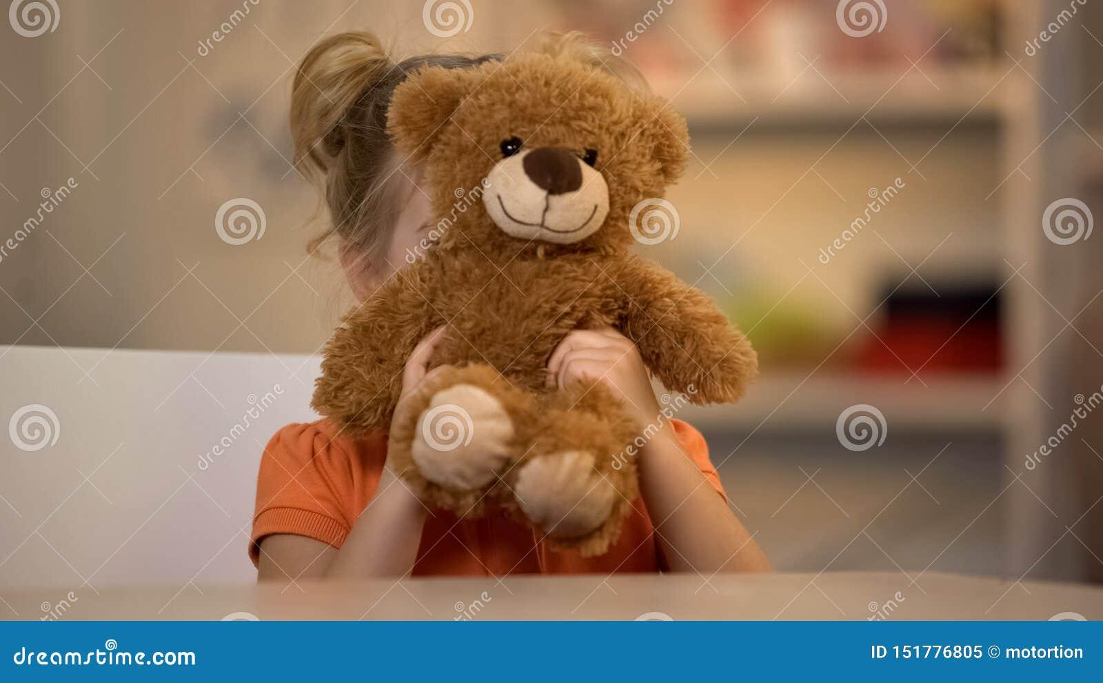 Aanbiddelijk glimlachend meisje die bruine teddybeer, blij jong geitje, gelukkige kinderjaren houden